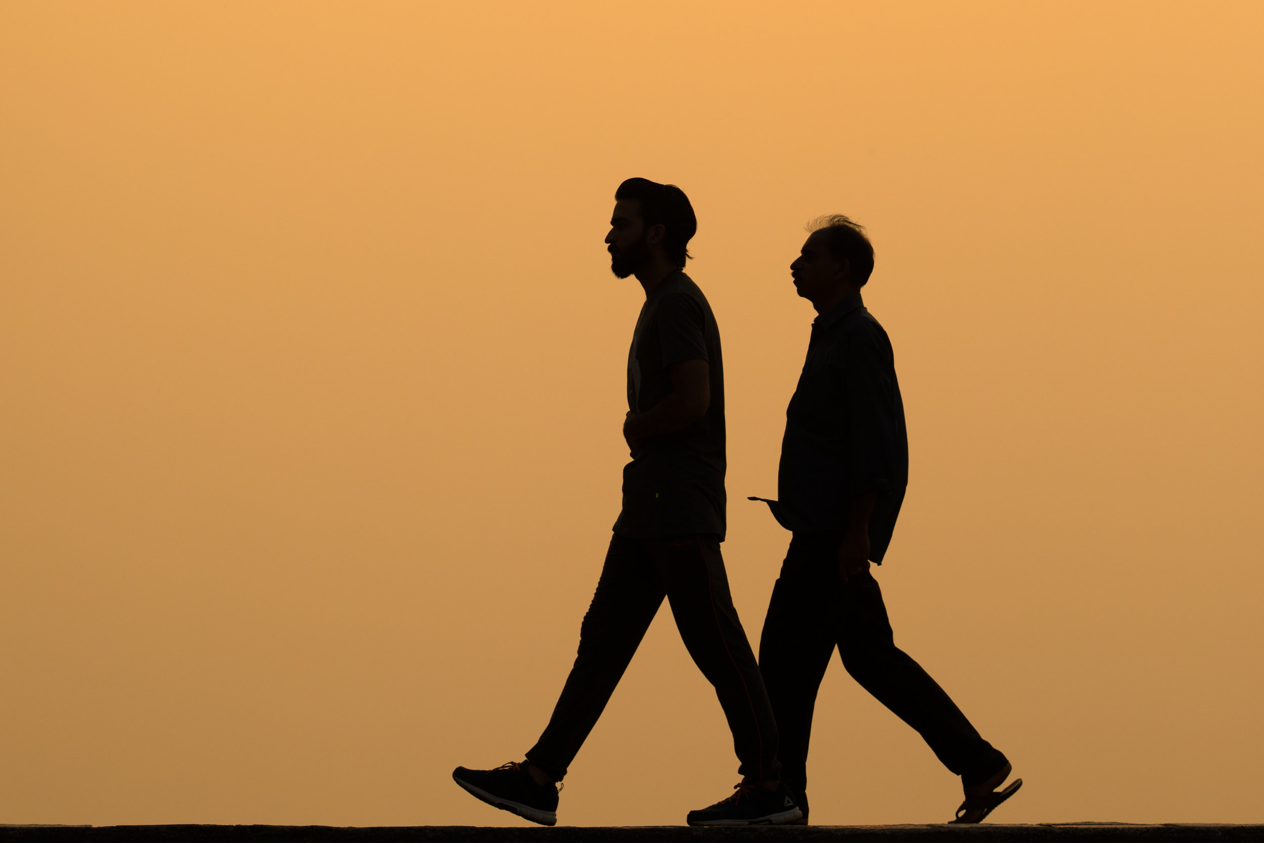 Silhouetted walkers at Sunset in Kochi, India.