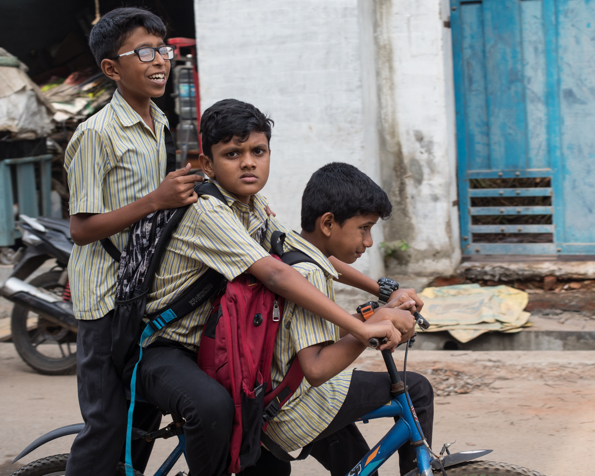 Three boys sharing a bike on the way home from School, Kerala.