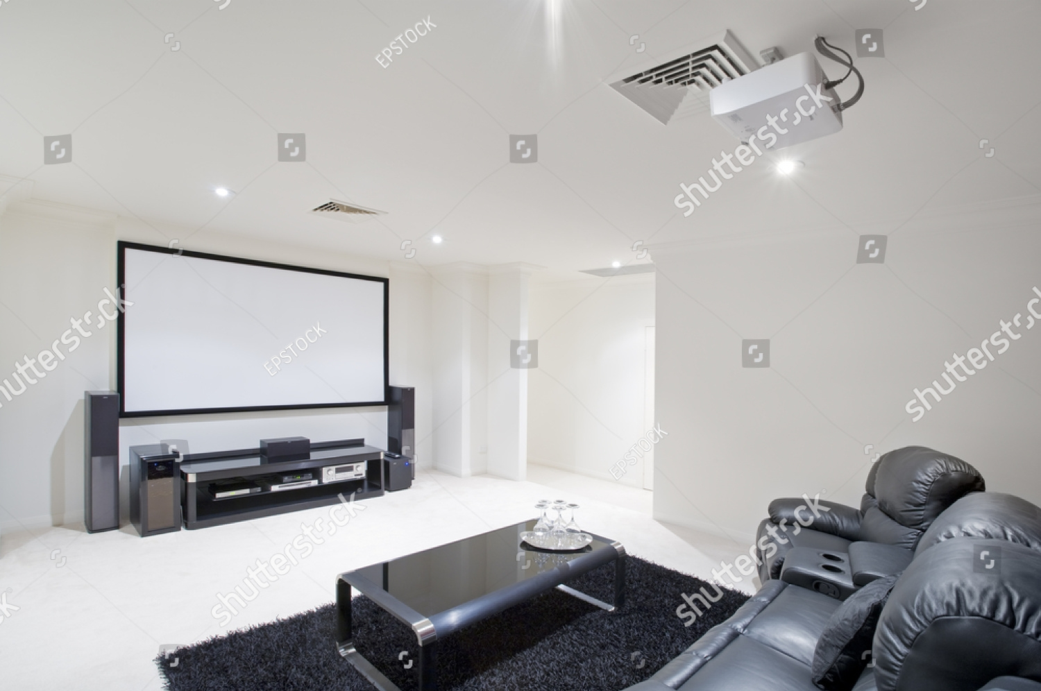stock-photo-home-theater-room-with-black-leather-recliner-chairs-black-rug-and-table-with-wine-glasses-41025172.jpg