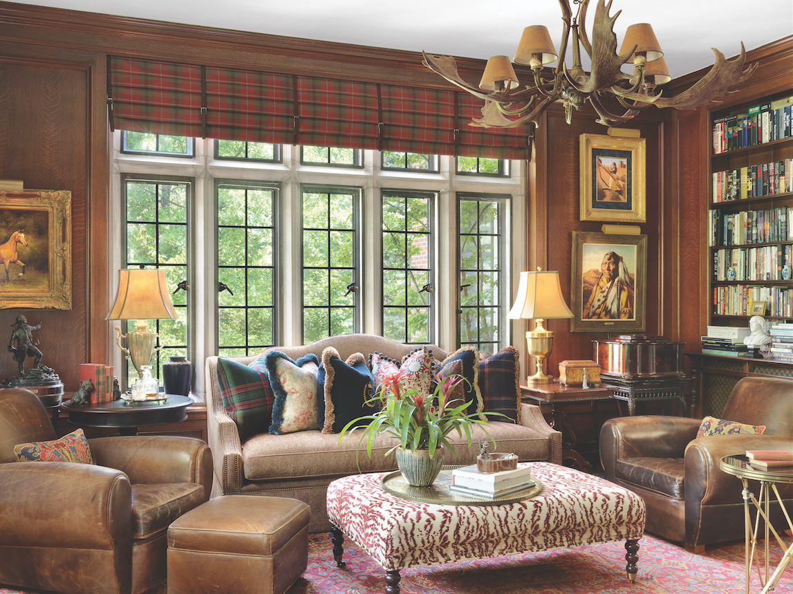 Leather and plaid bring traditional style to the wood-paneled library, awash in light from a wall of clerestory over casement windows.