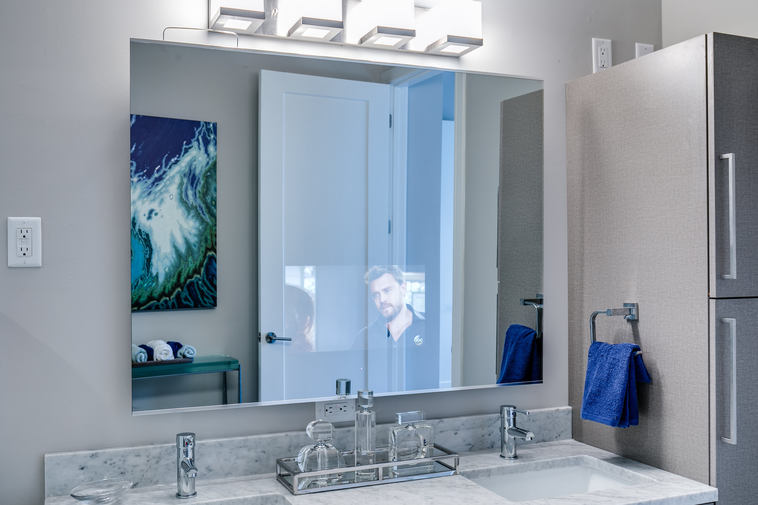 A TV inside the master bathroom mirror in a unit at The Barton.
