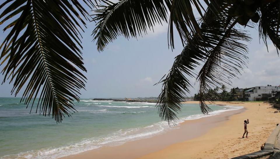 In this Friday, May 10, 2019, photo, a boy walks on a beach in Hikkaduwa, Sri Lanka. (AP Photo/Eranga Jayawardena)