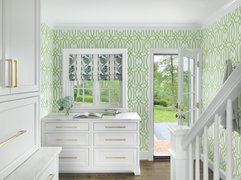 Too pretty to be the back entrance, the mudroom/rear staircase is springtime cheerful with custom white cabinetry and trellis wallpaper.