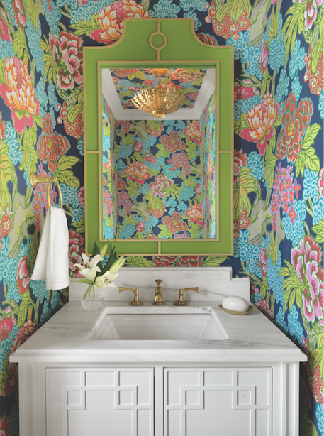 An existing powder room is artfully reinvented with a golden chandelier and spectacular wallpaper.