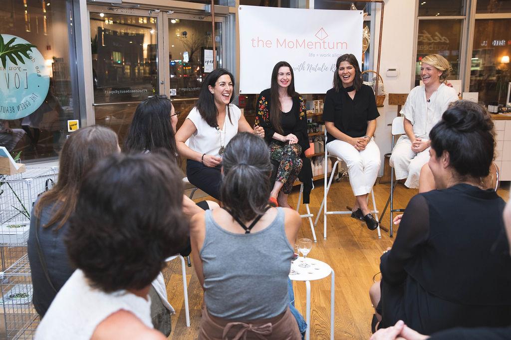 a_circle_of_women_on_stools_listening_to_Natalie_Ruskin_MoMentum_talk.jpg