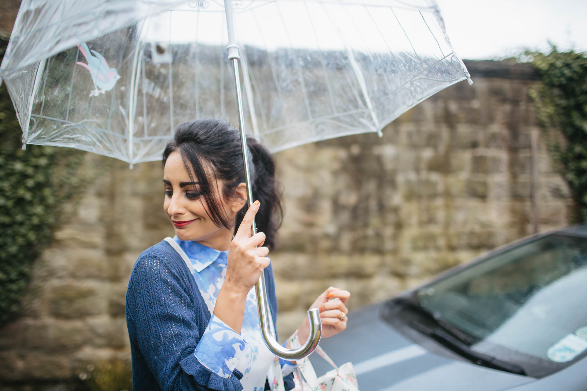 Bridesmaid holding an umbrella on her way to the wedding