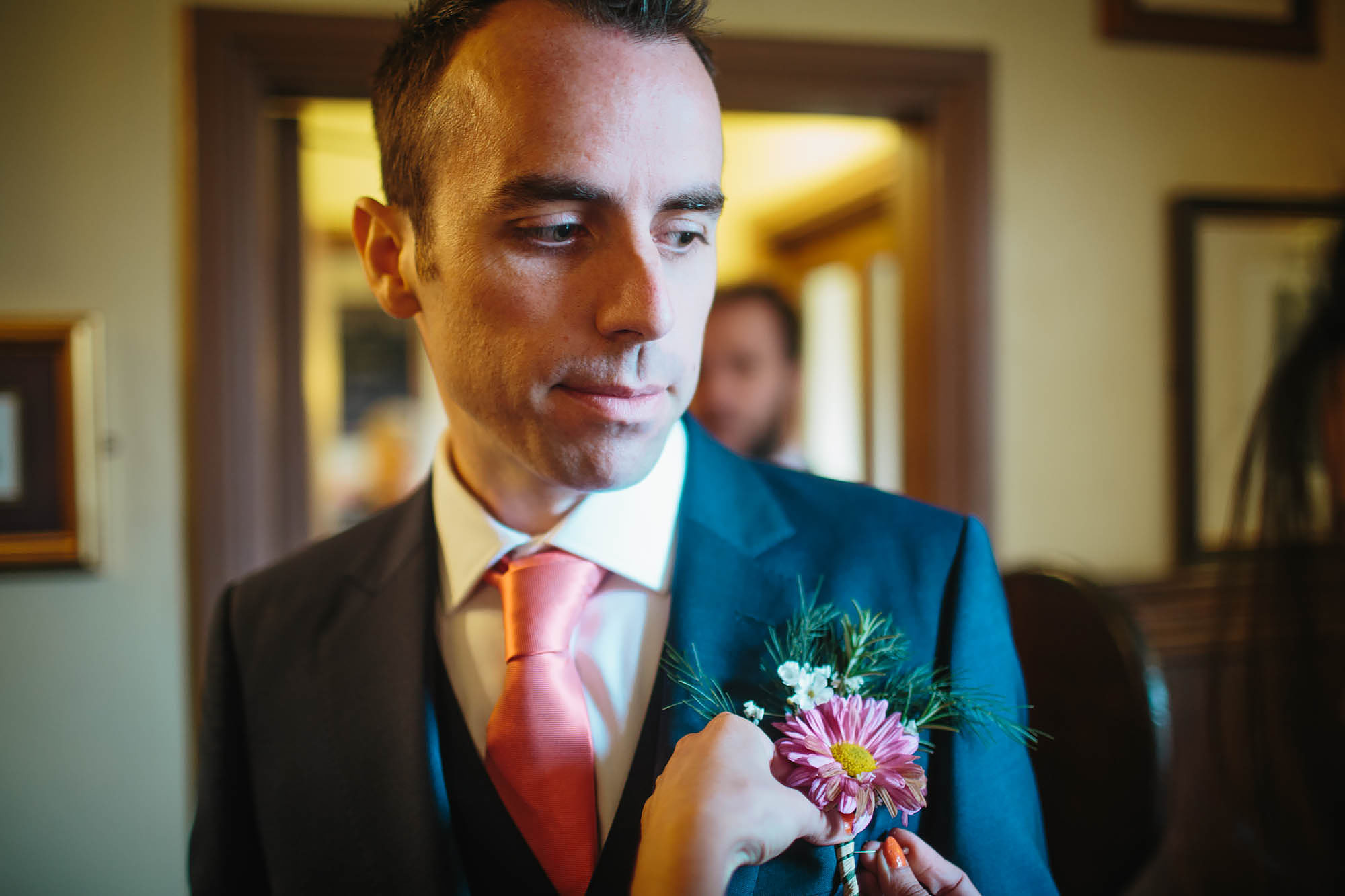 Groom on his wedding day has his buttonhole attached
