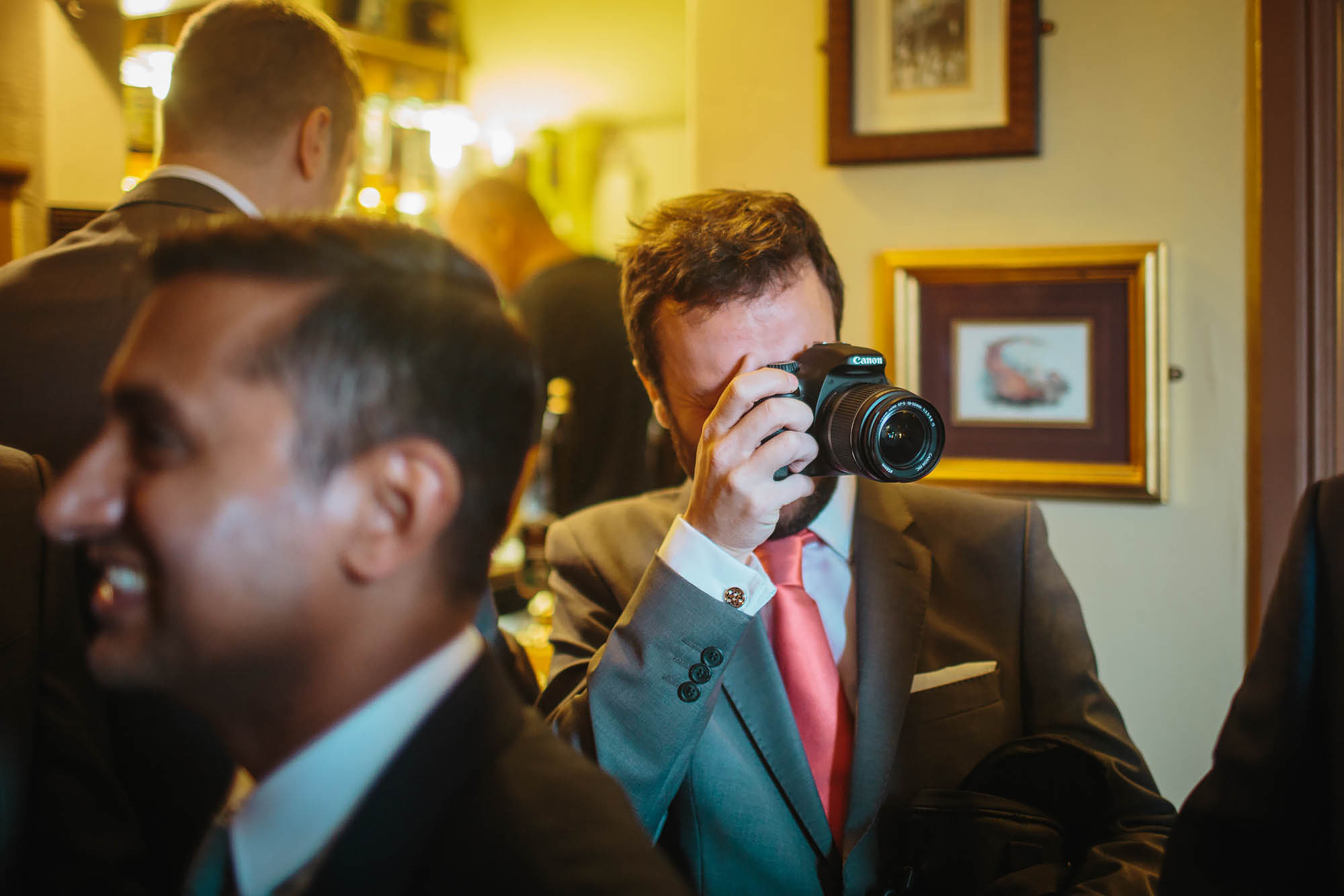 Best man taking photographs with a camera on the wedding day