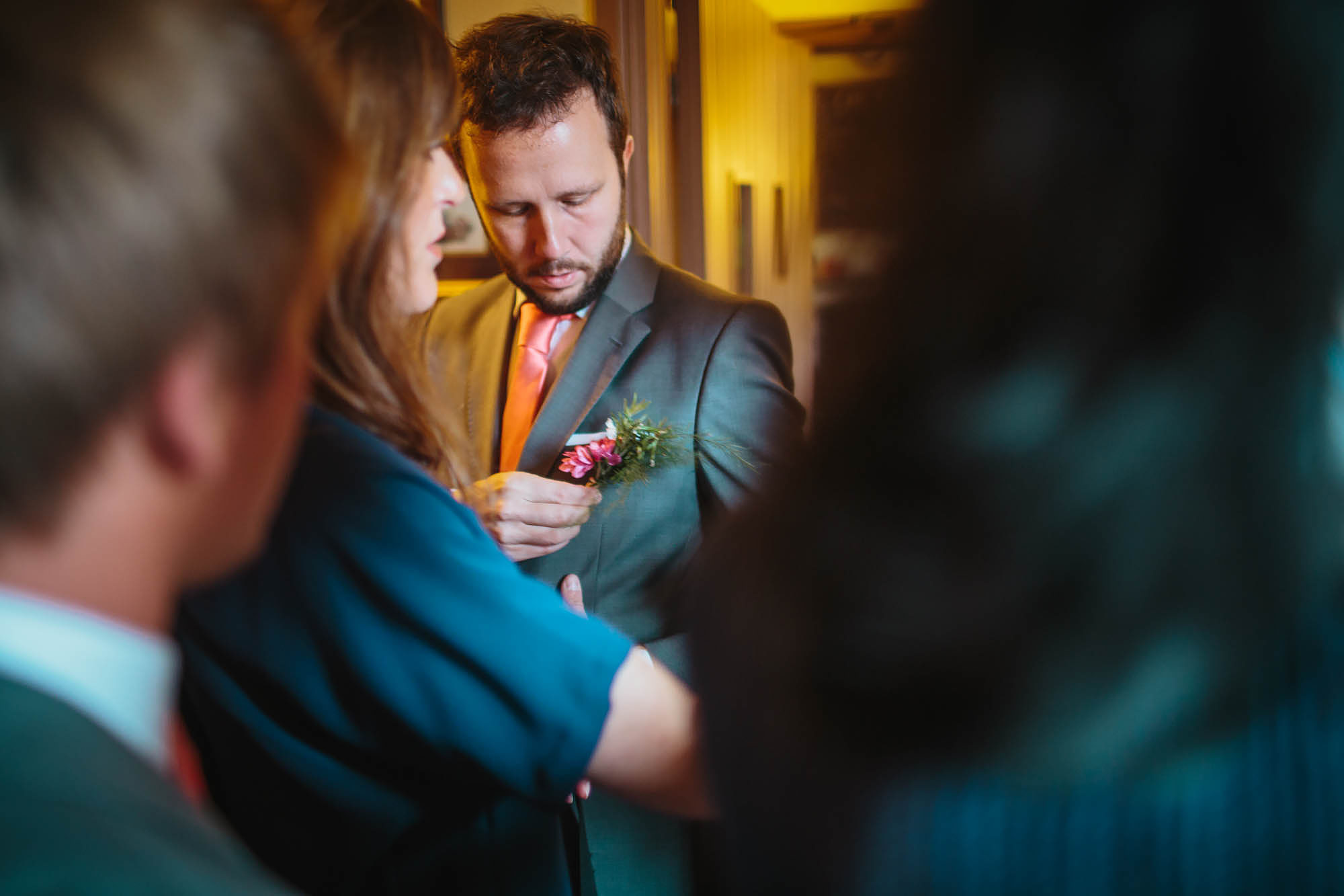 Best man attaches his buttonhole and flower on the wedding day in Yorkshire
