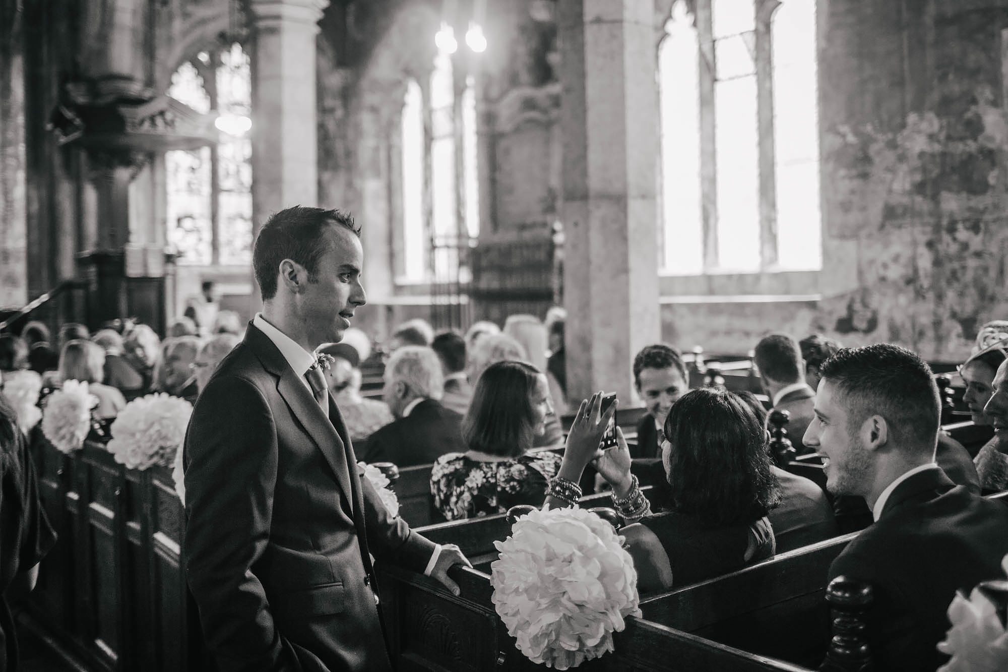 Groom chatting to guests in the church at his wedding in Yorkshire