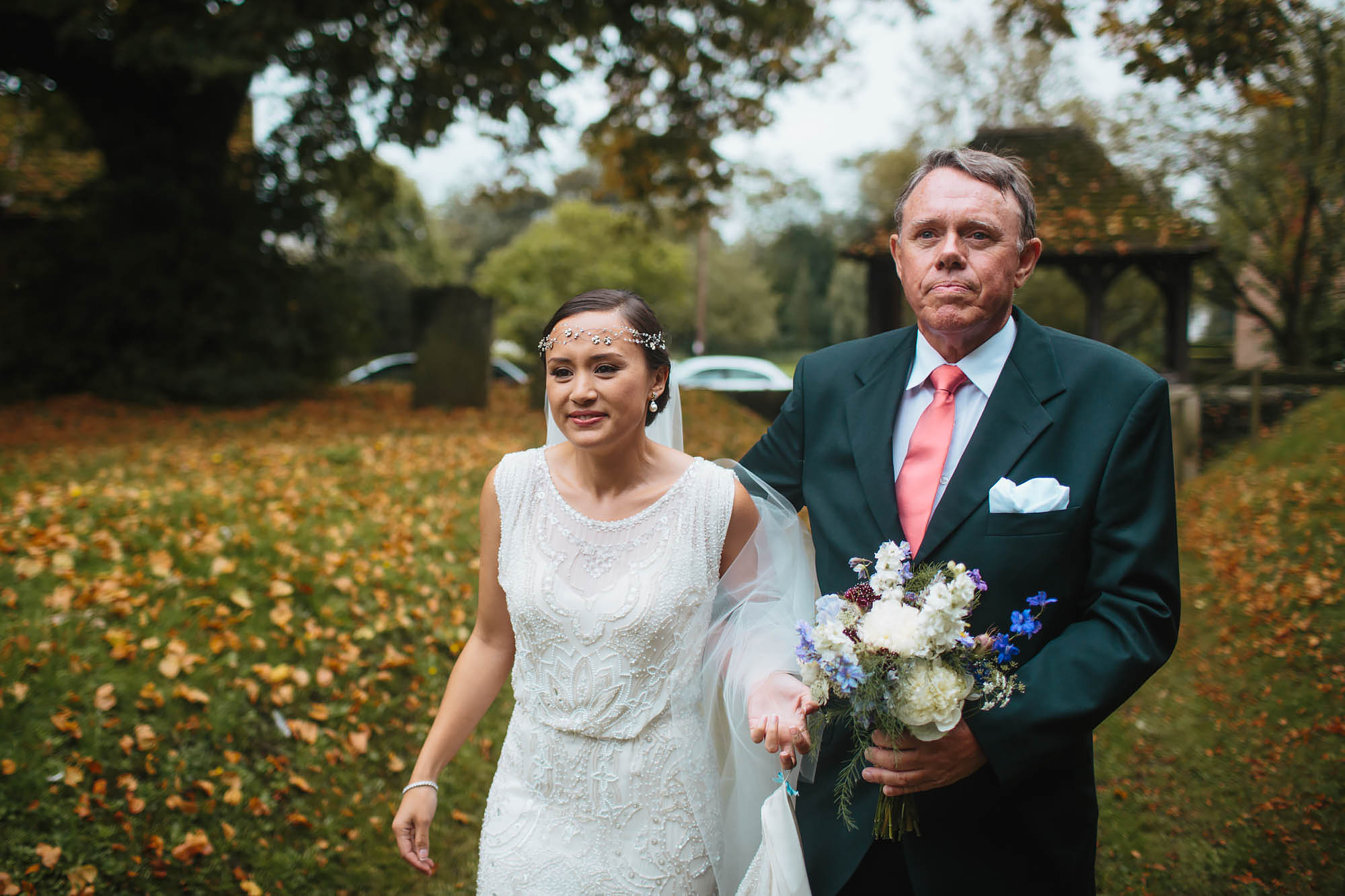 Bride walks to the church with her father on her wedding day