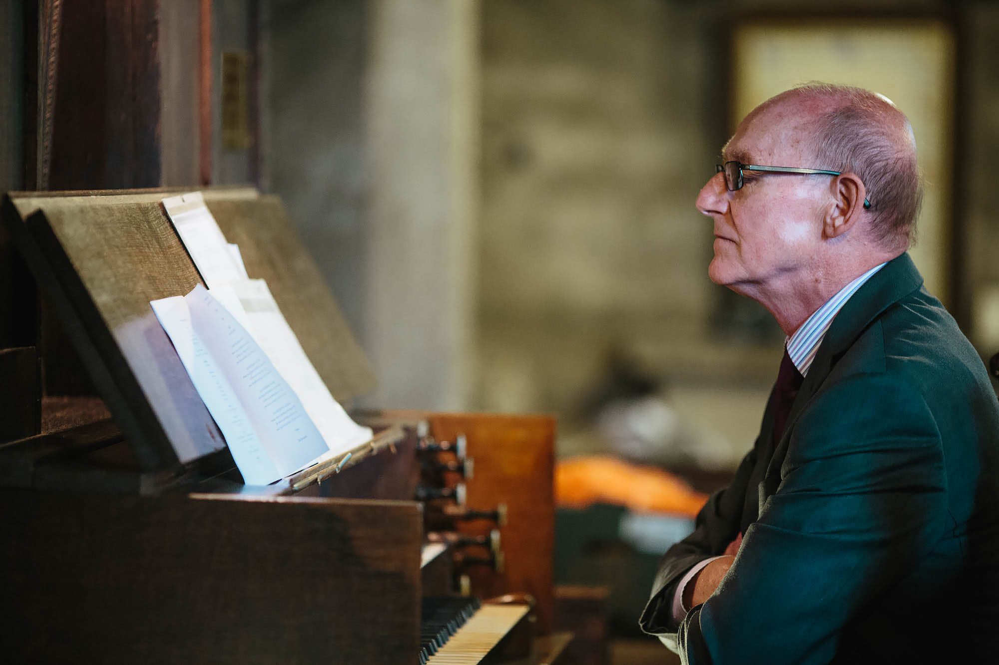 Church organist looks at his music during the wedding ceremony