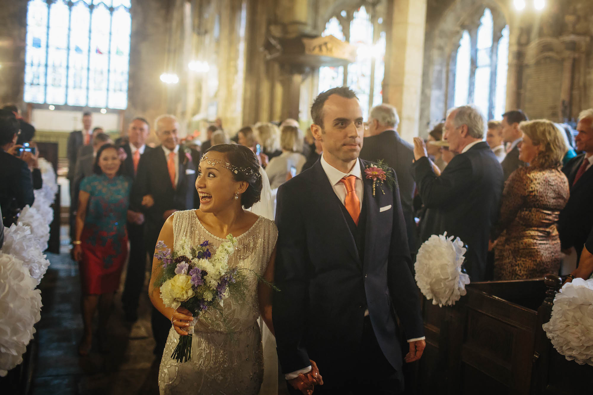 Bride and groom walk down the aisle of a church at their wedding