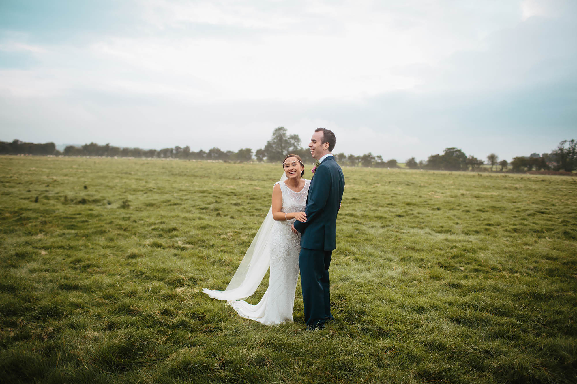 Bride and groom laughing in a field at Hornington Manor