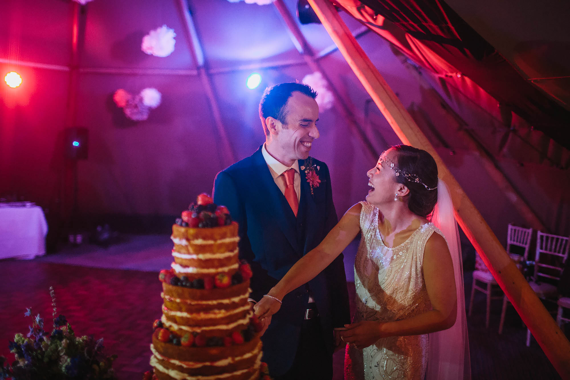 Bride and groom laughing as they cut the cake at Hornington Manor