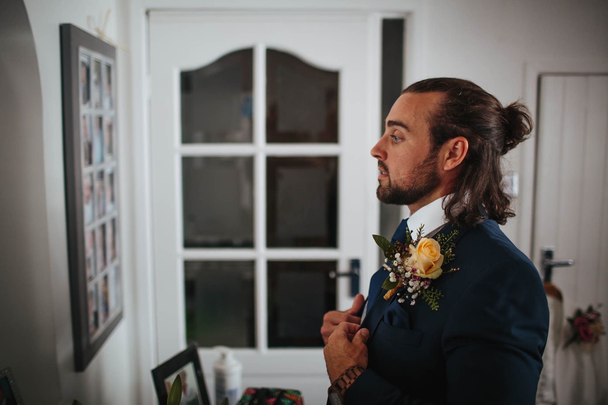 Groom looking in the mirror getting ready on his wedding day