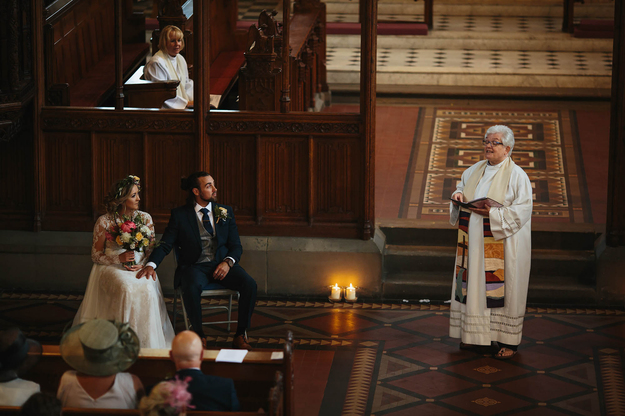 Bride and groom look to the vicar during the wedding ceremony in Manchester