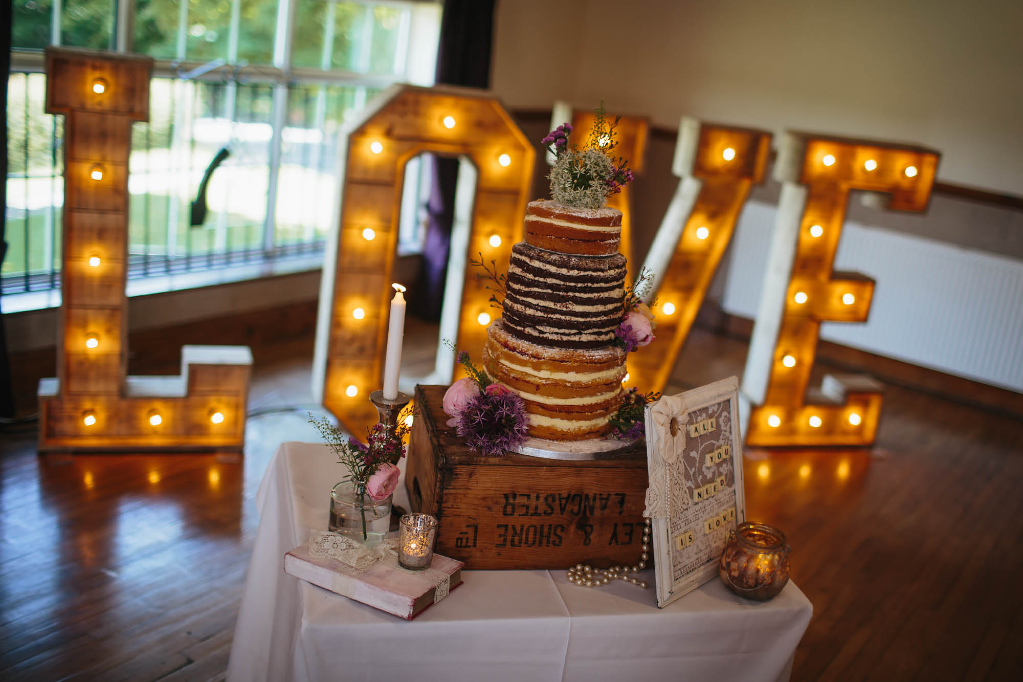 Wedding cake in front of love sign