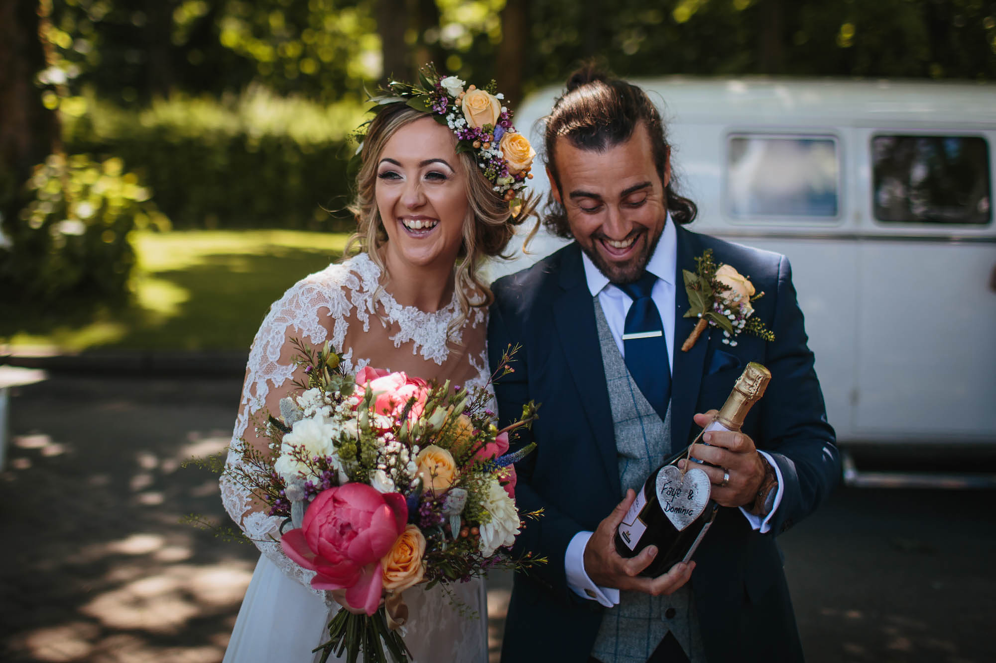 Bride and groom laughing as they hold a bottle of champagne at their wedding