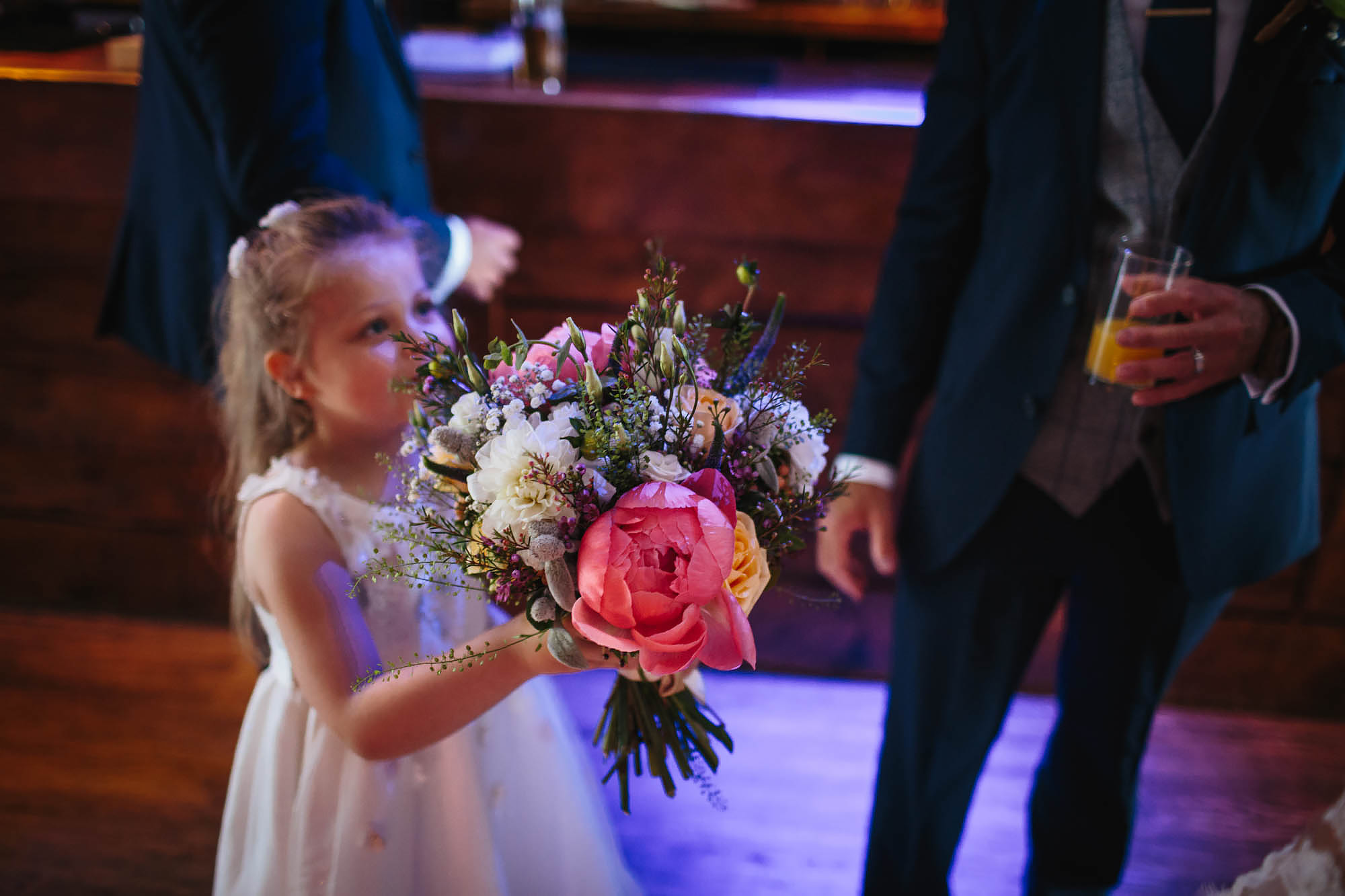 Flower girl holds the bouquet at a wedding