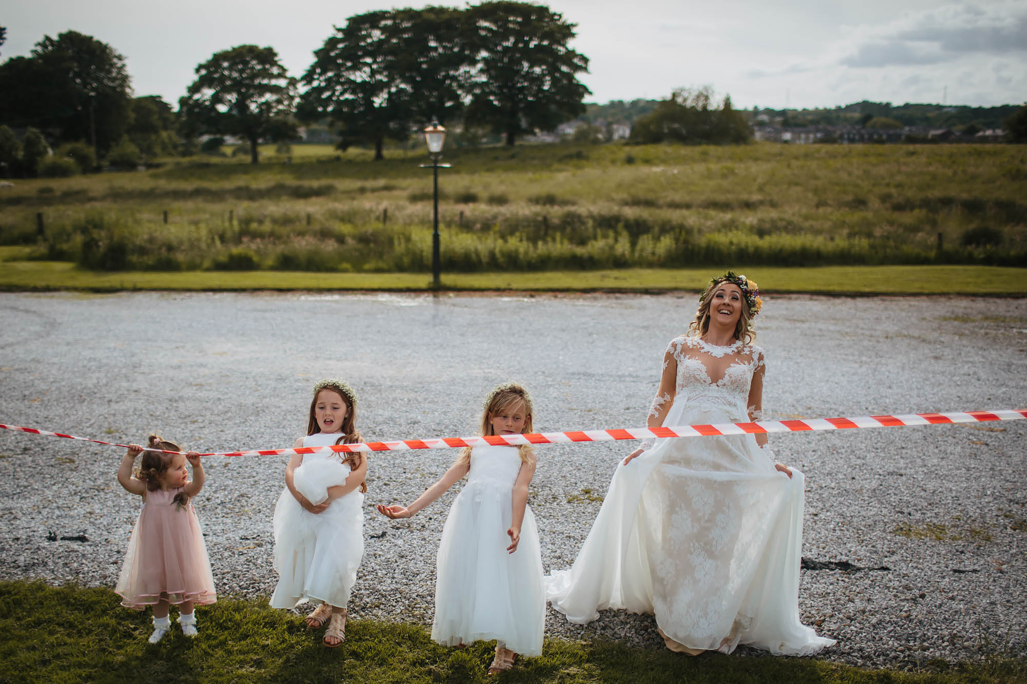Bride and bridesmaids limbo under red tape at a wedding