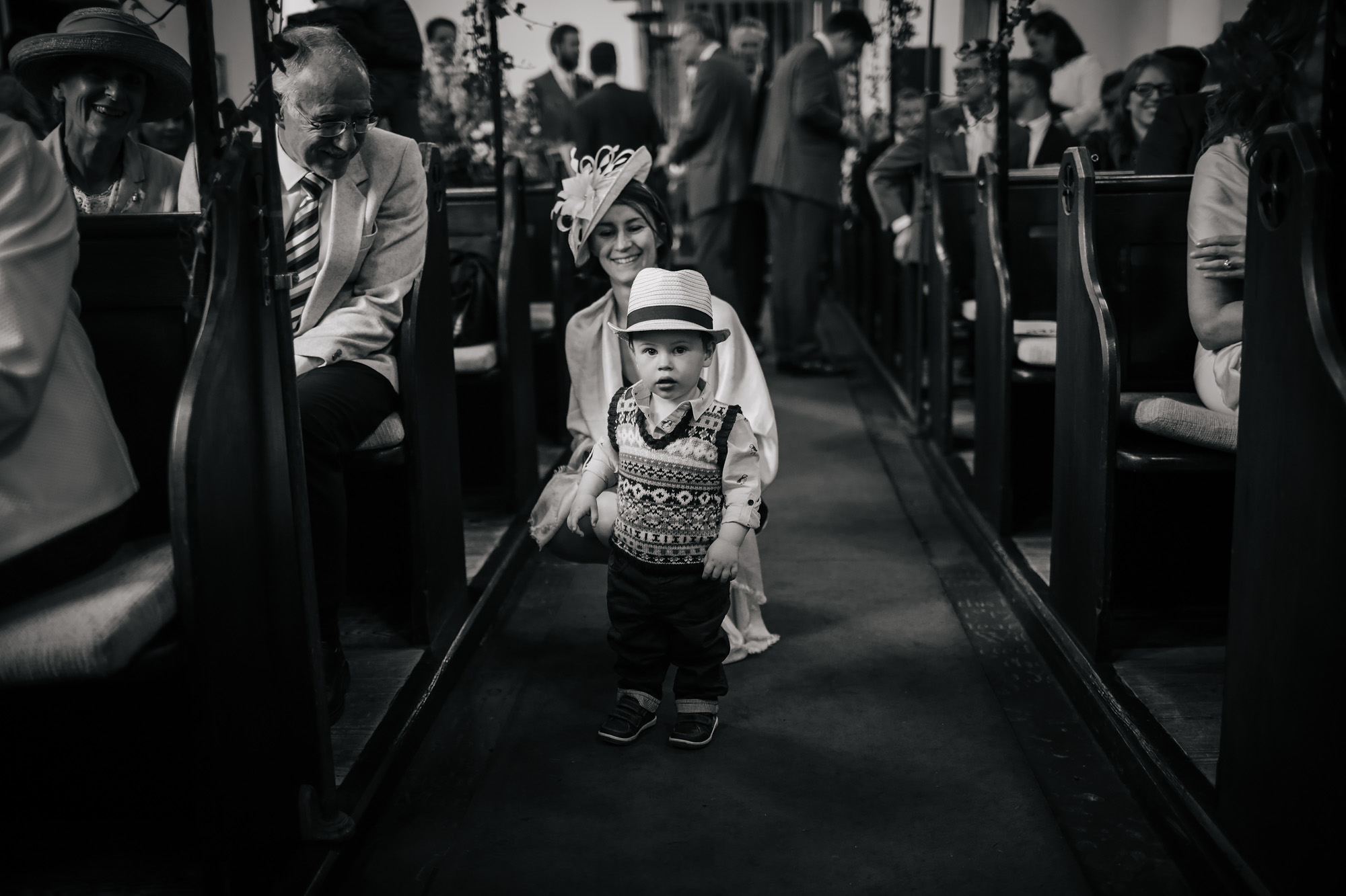 Boy with a hat in the church aisle during the wedding