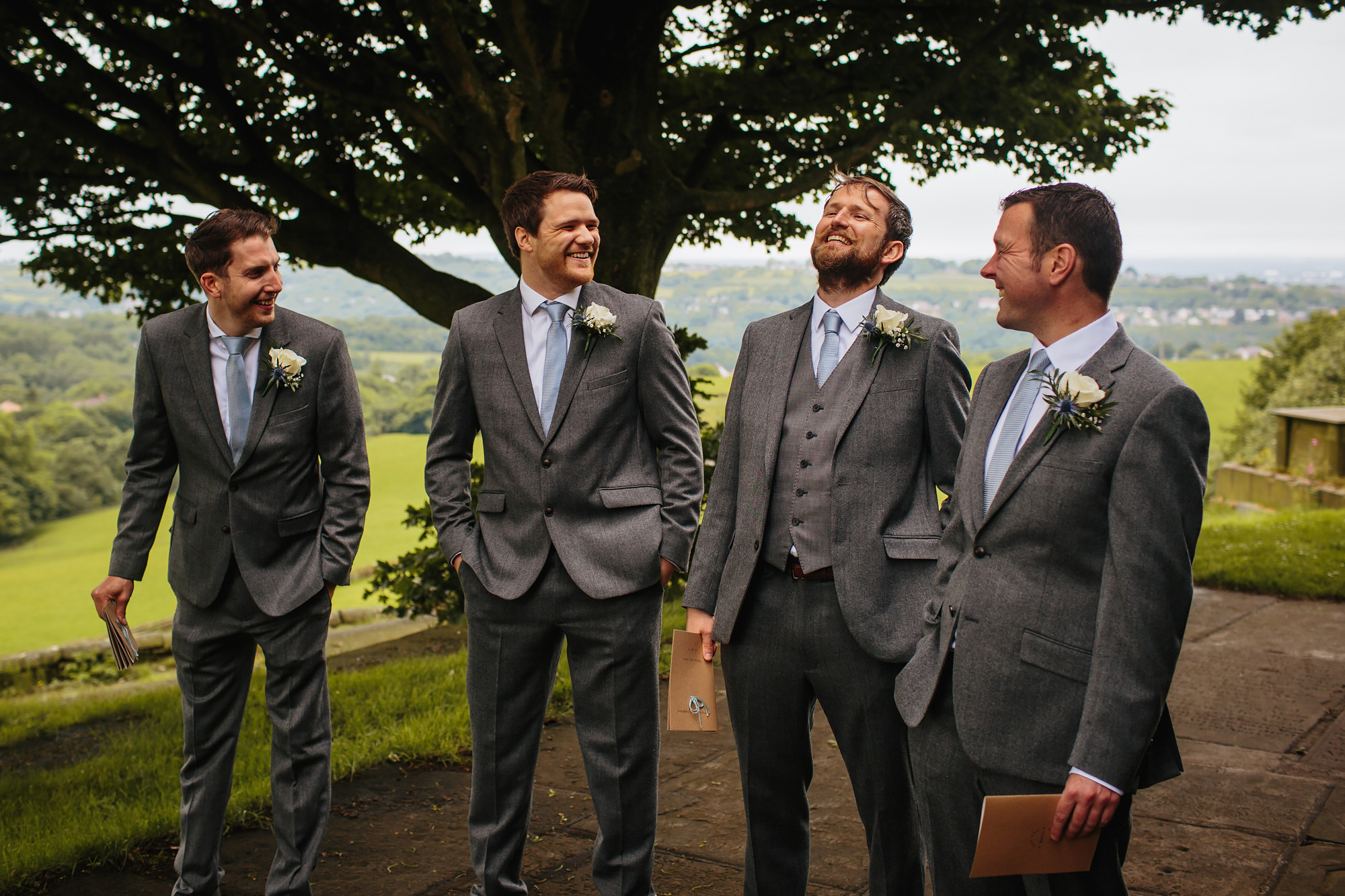 Groomsmen and ushers laughing outside the church