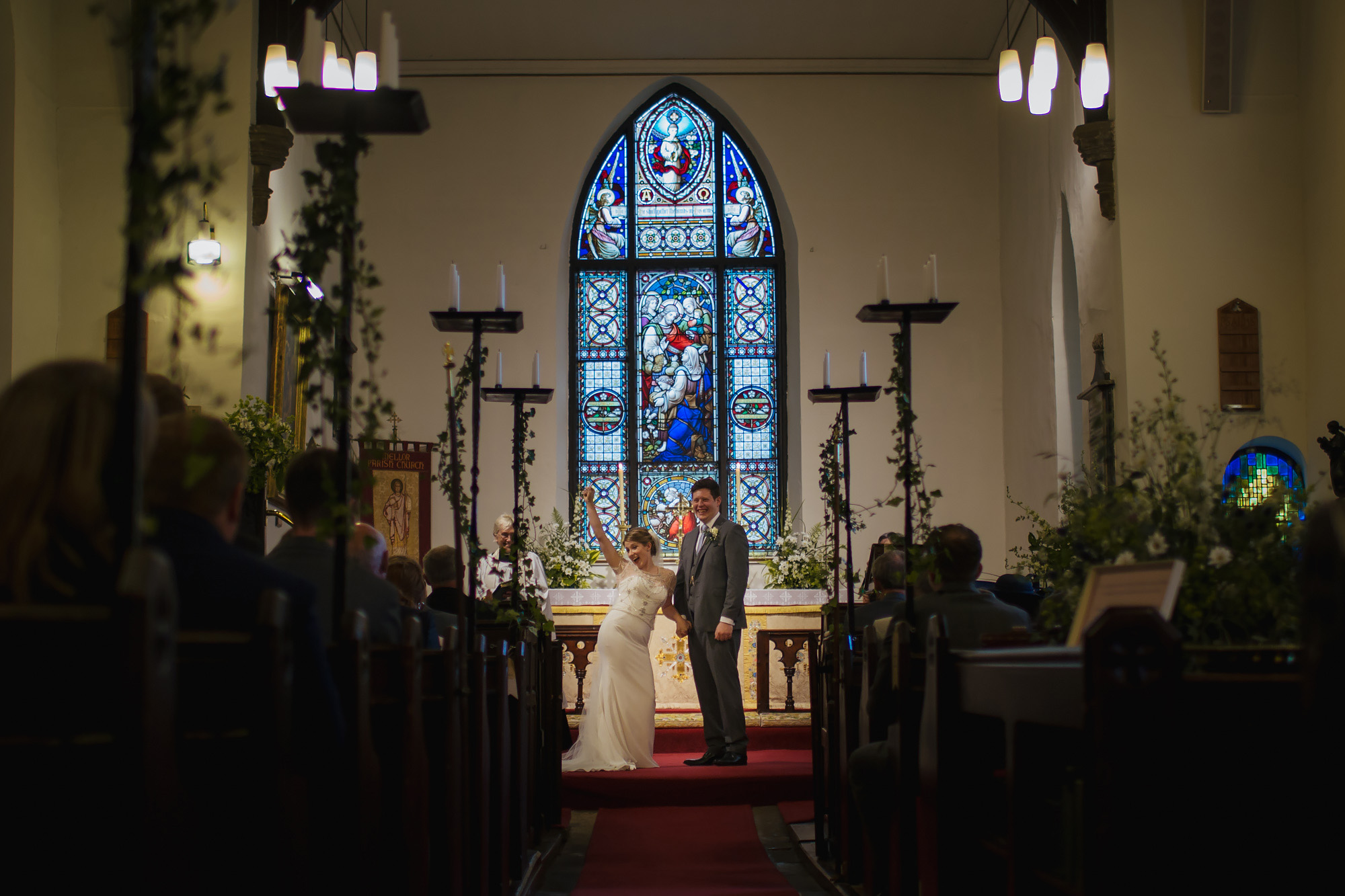Bride and groom happy at their church ceremony in front of a stained glass window