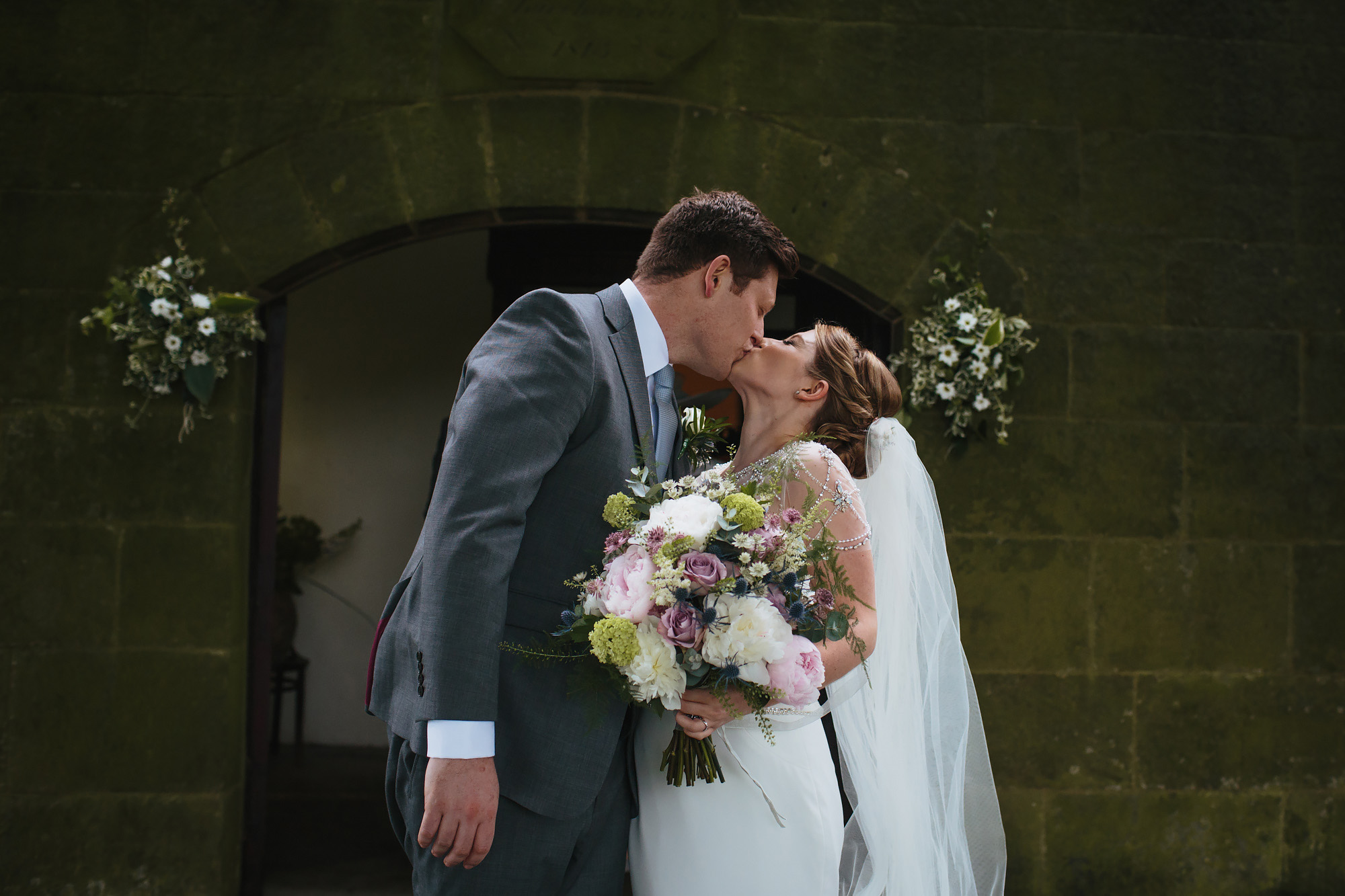 Bride and groom kiss outside the church after their wedding