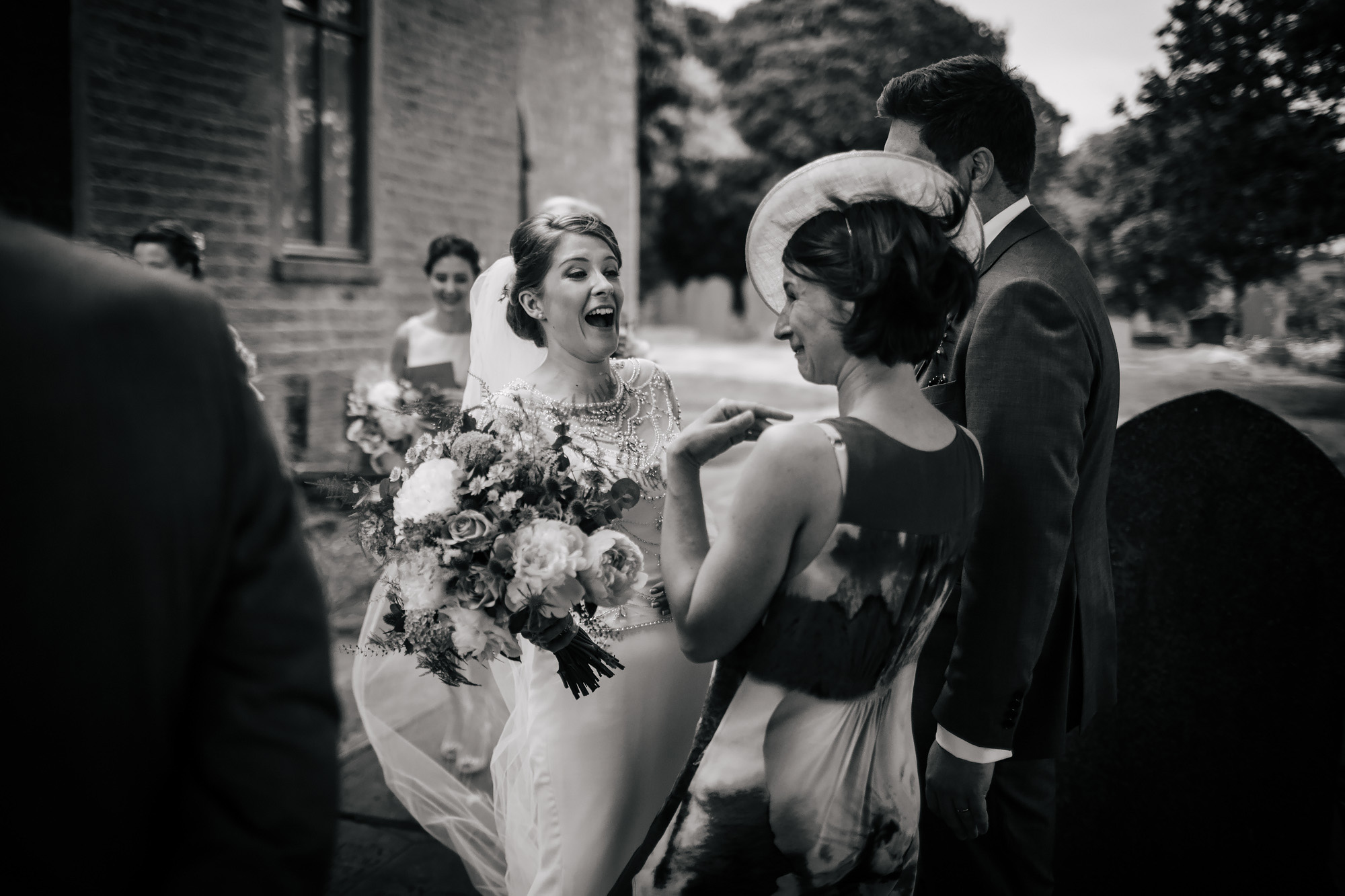 Bride laughing with guest outside the church