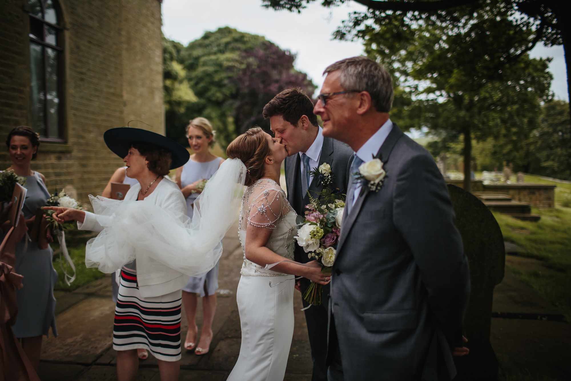 Bride and groom kissing in front of their families