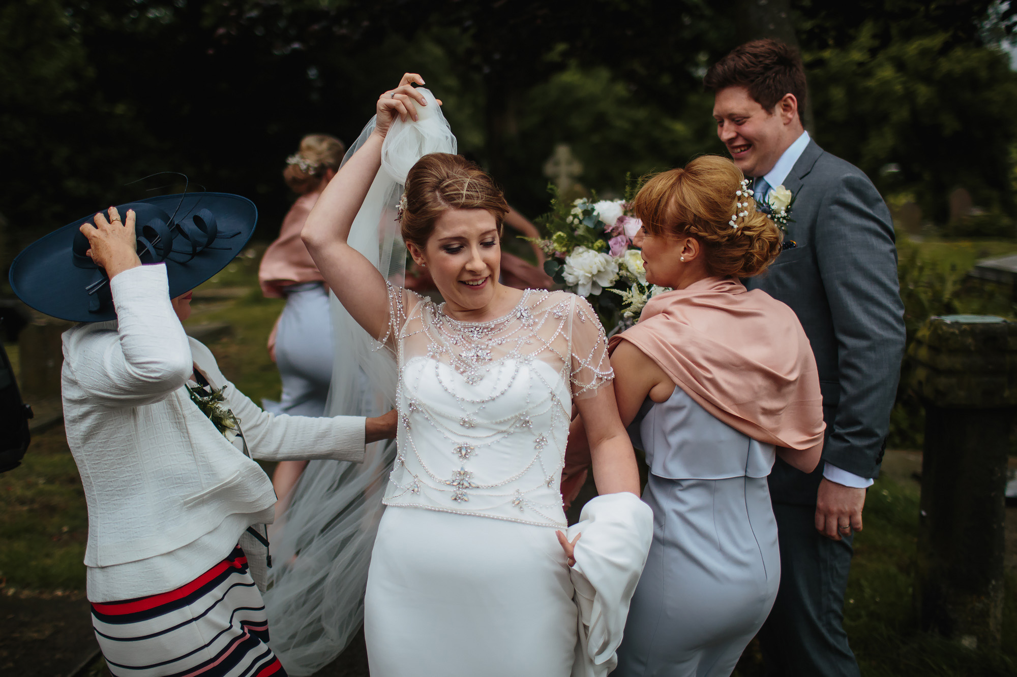 Bride hold her veil on a windy day at her wedding in Lancashire
