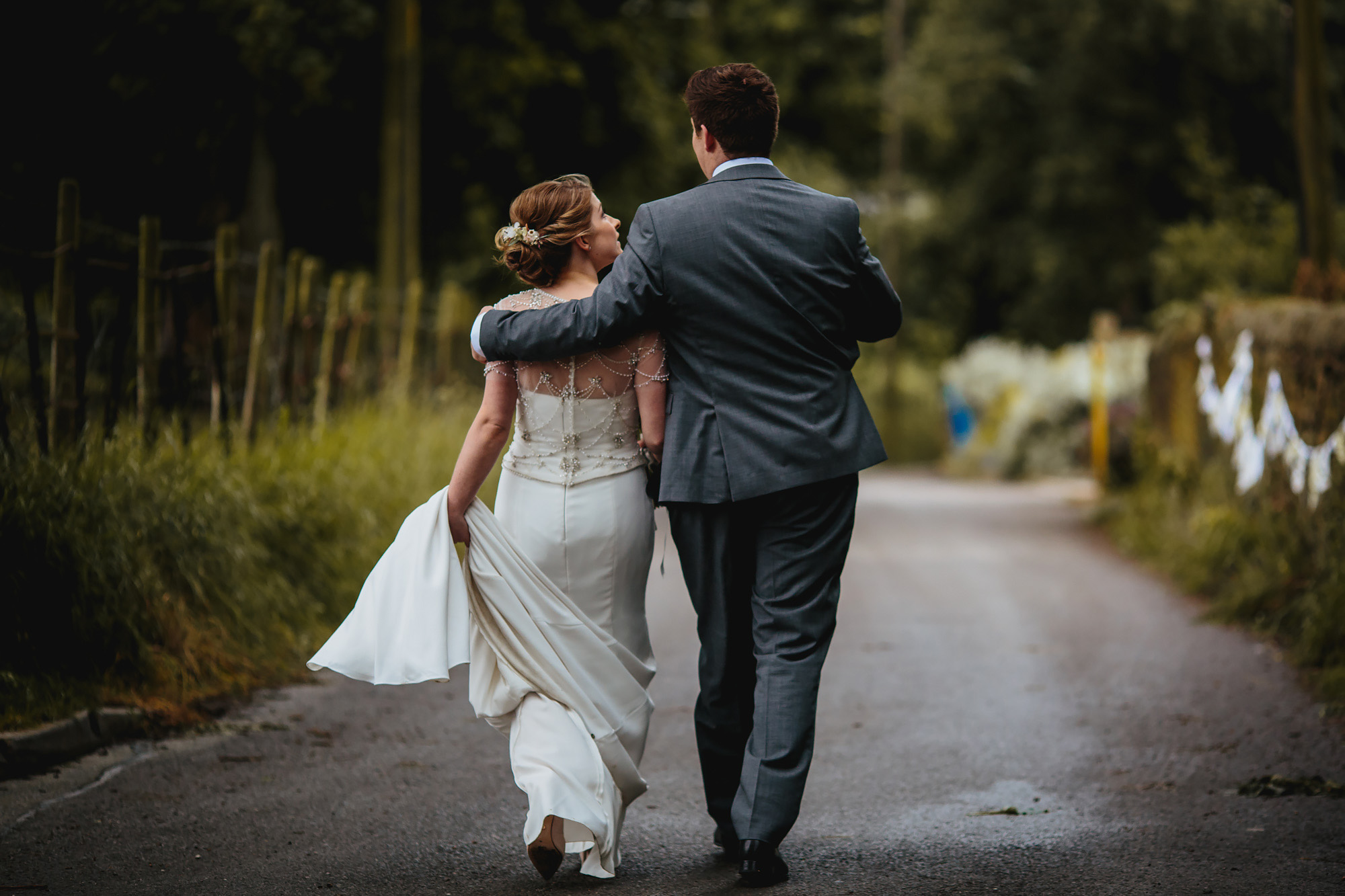Happy bride and groom walking away with arms round each other