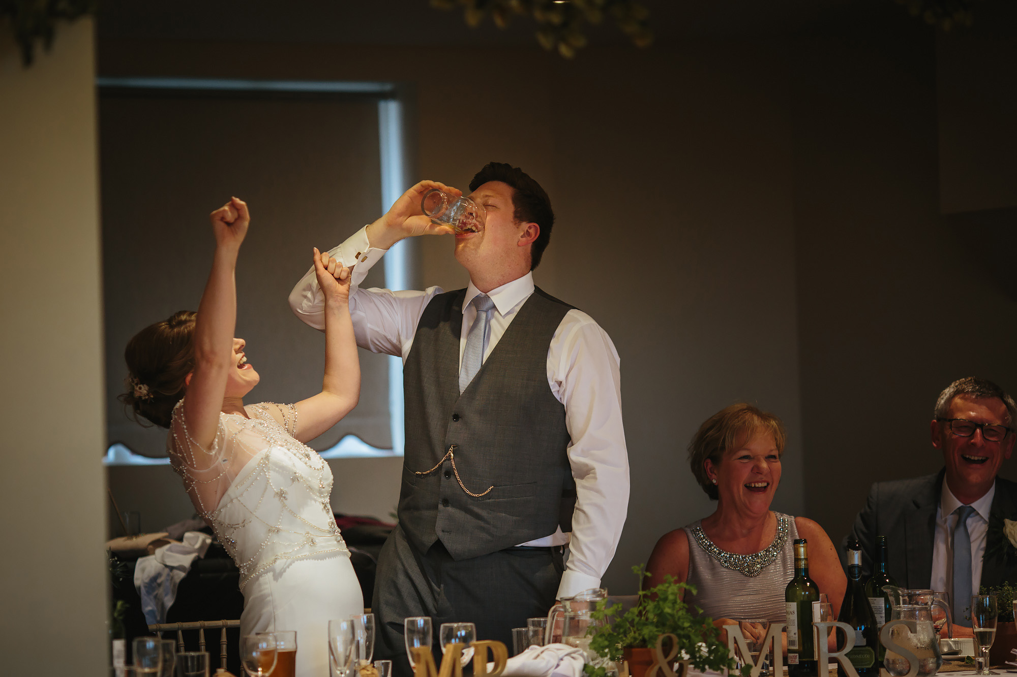 Groom drink a pint and his wife celebrates at a village hall wedding