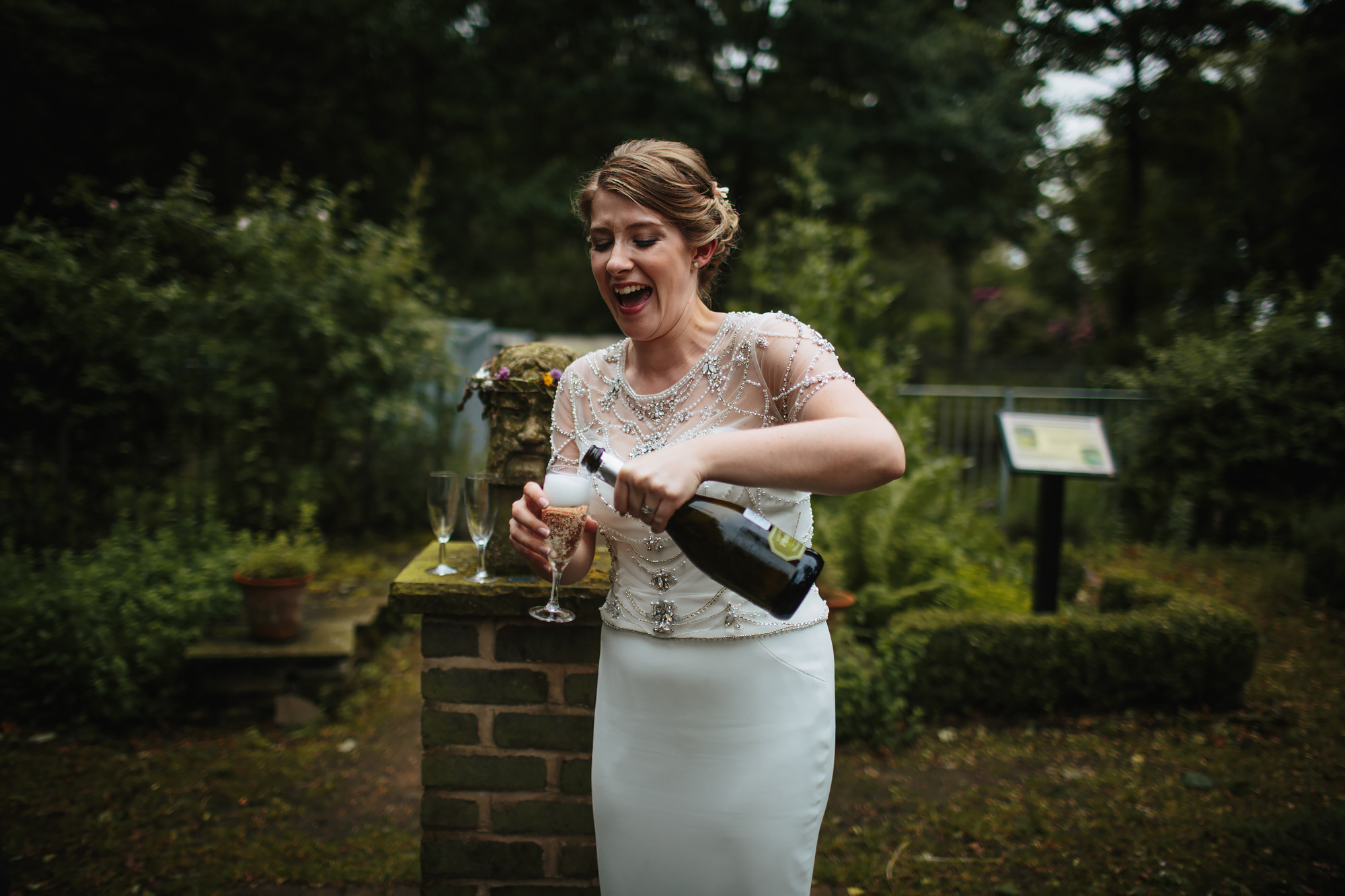 Bride laughing while she pours a glass of champagne