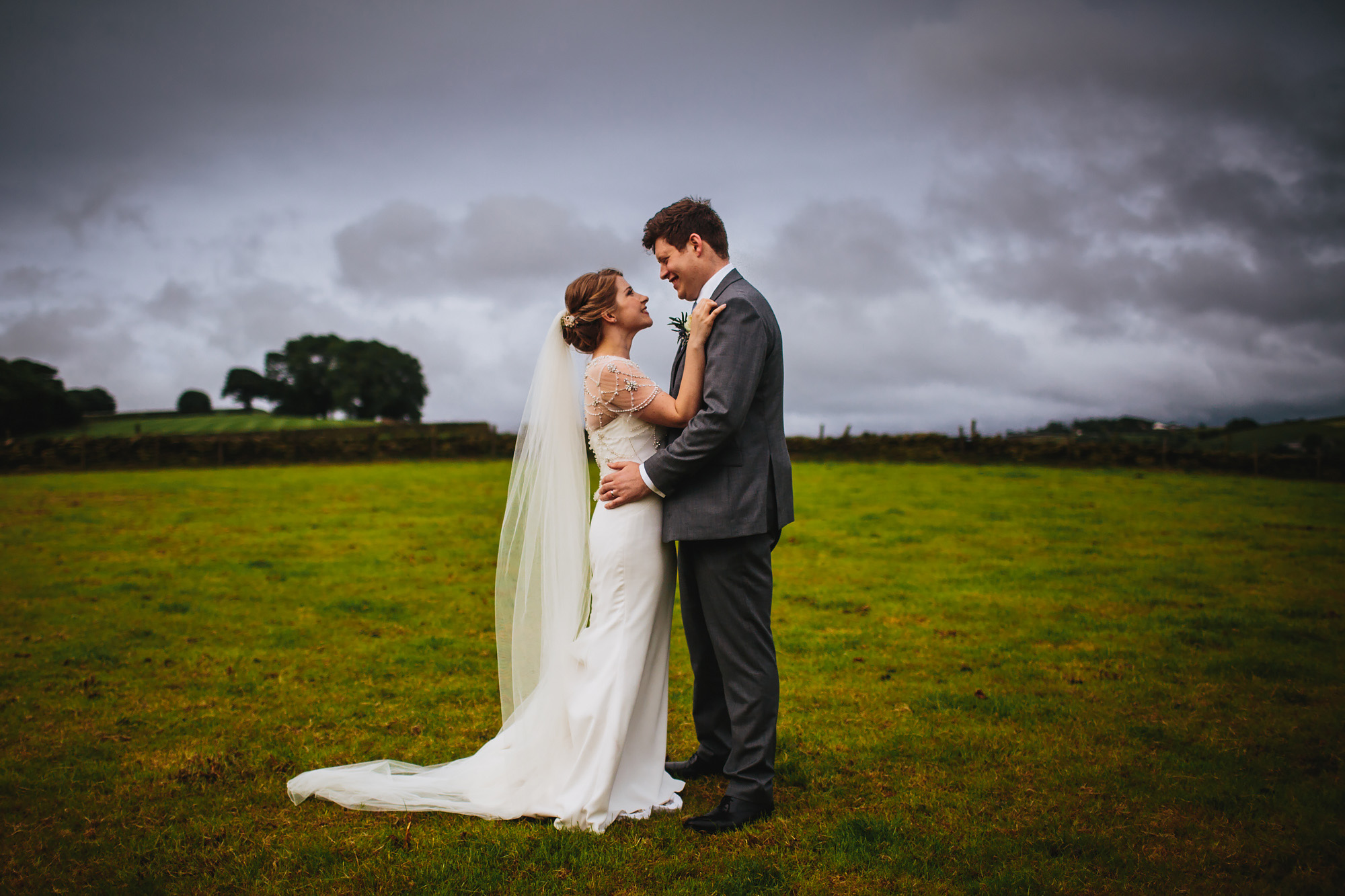 Bride and groom smiling at each other in a field