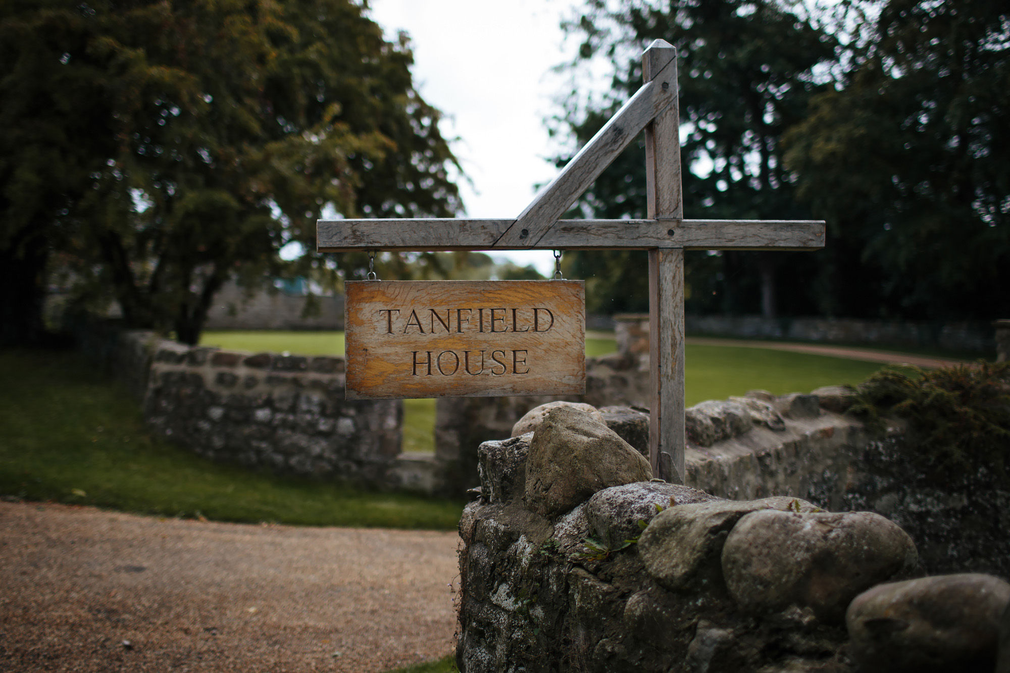 Wooden sign for Tanfield House by brick wall
