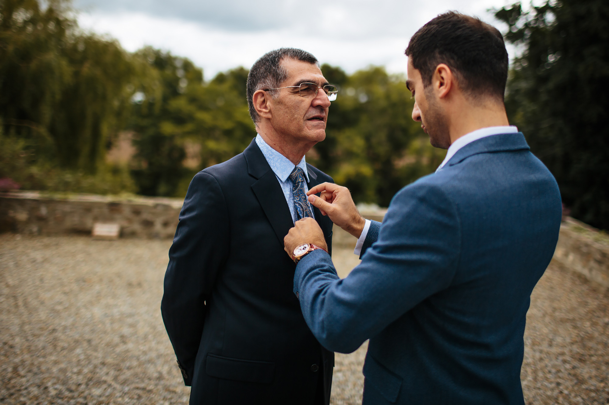 Groom adjusts fathers tie and suit for the wedding