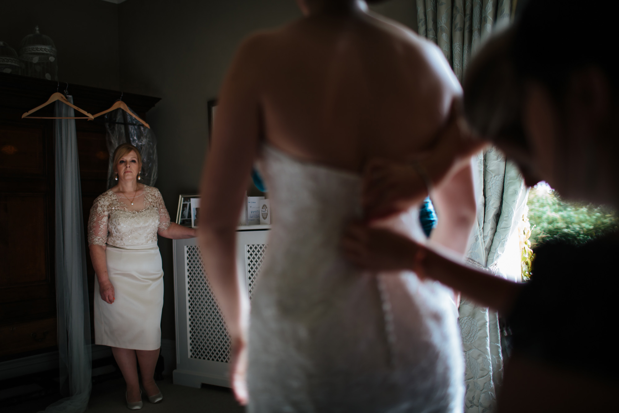 Brides mother watches her daughter have her dress buttoned up