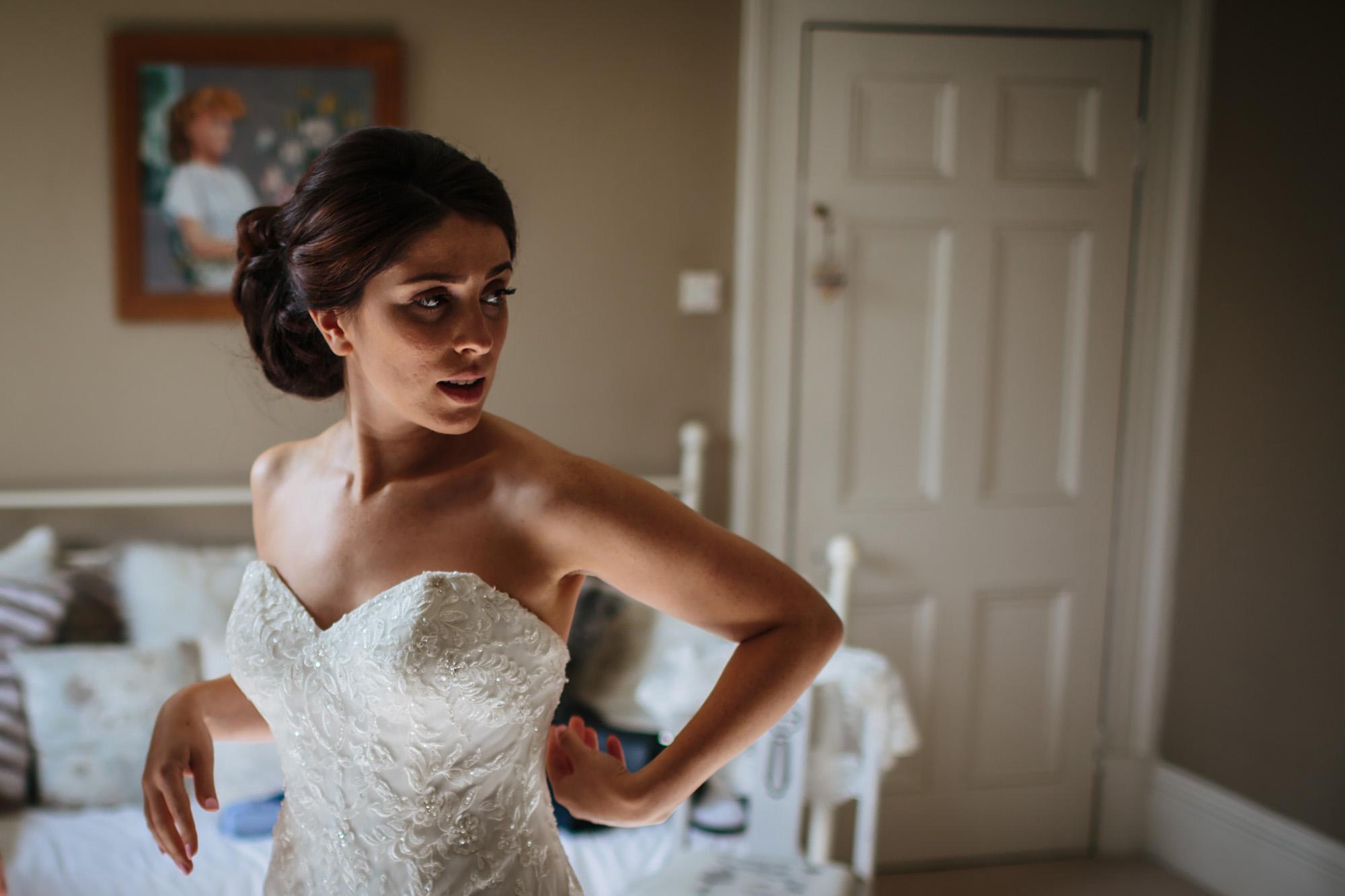 Pretty bride adjusting her wedding dress