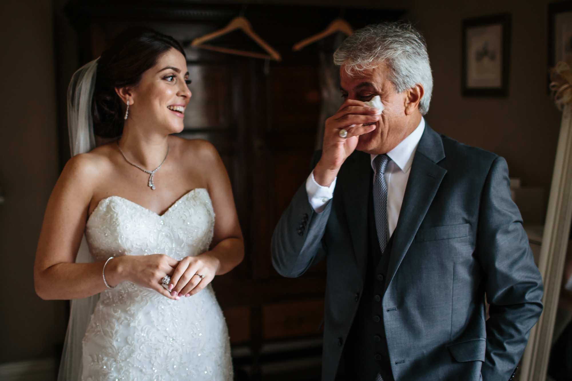 Brides father wipes away a tear and bride laughs