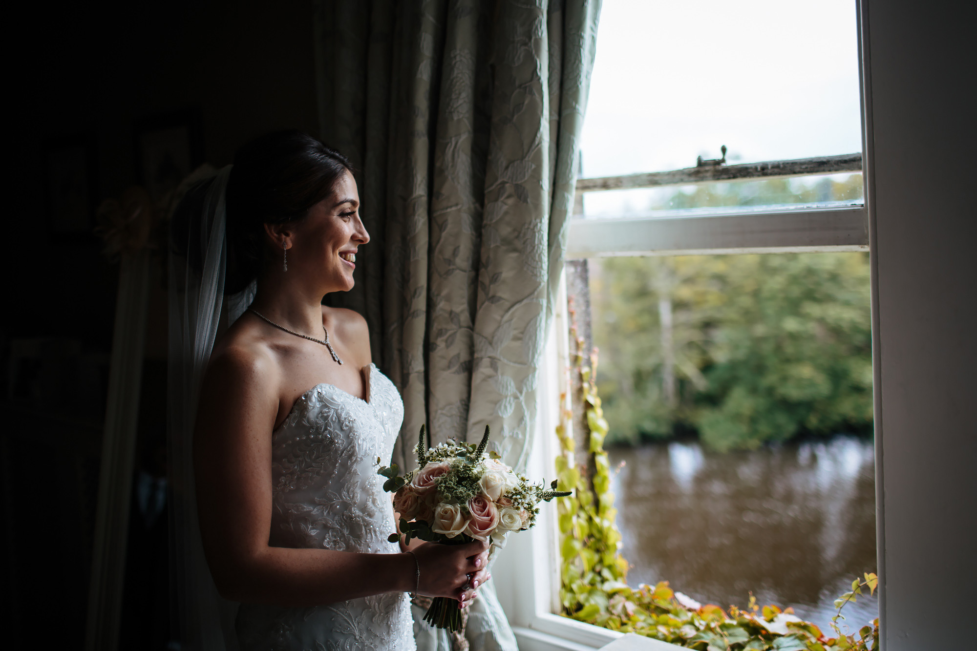 Bride holds her flowers by the window on her wedding day