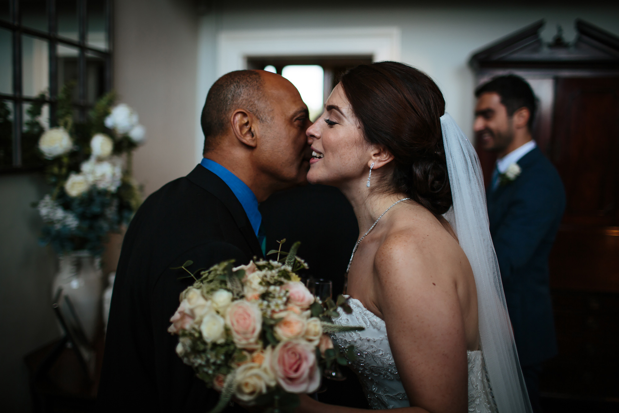 Bride with flowers kissing guest at her wedding