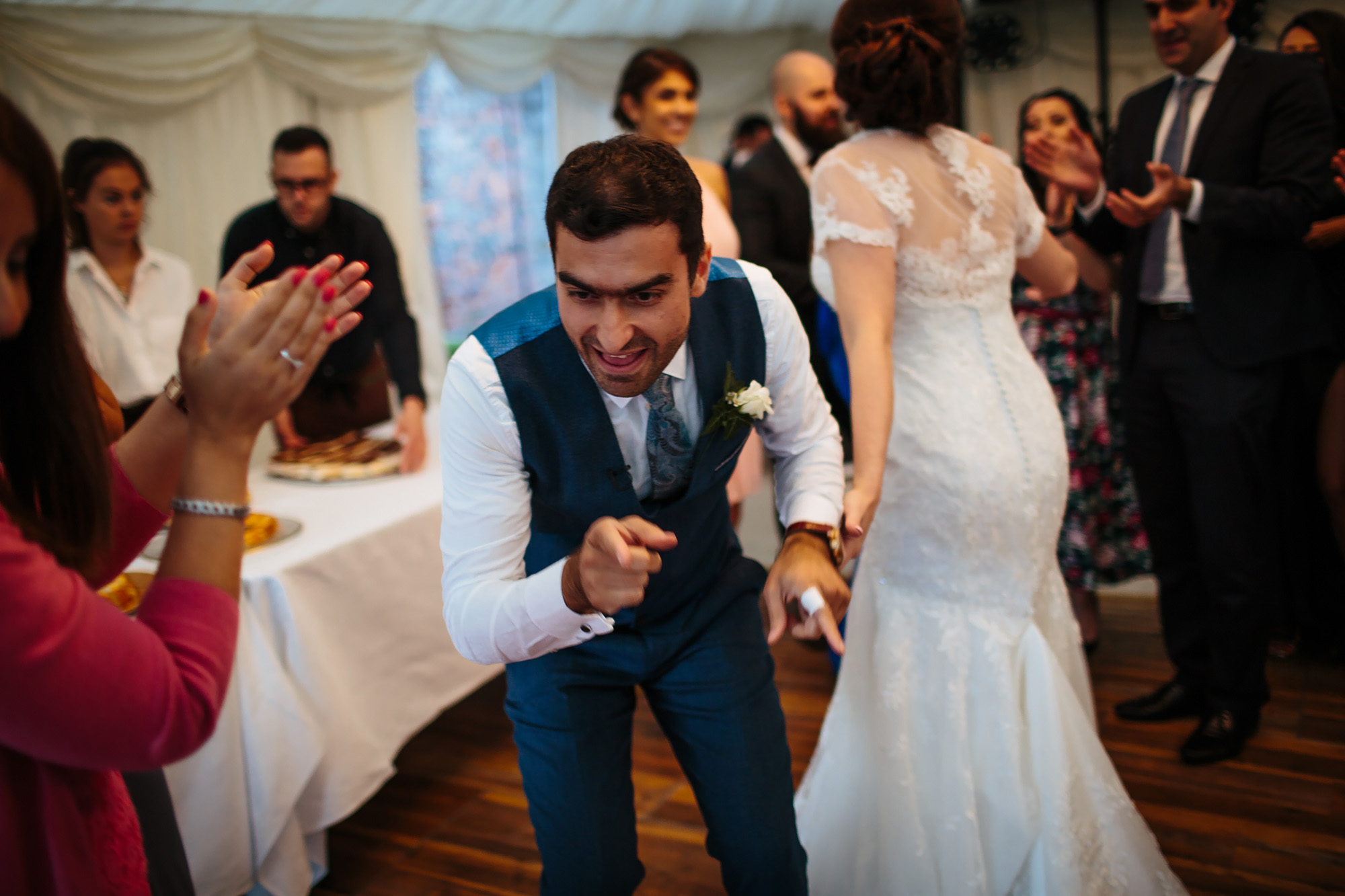 Groom dancing at a wedding with a child