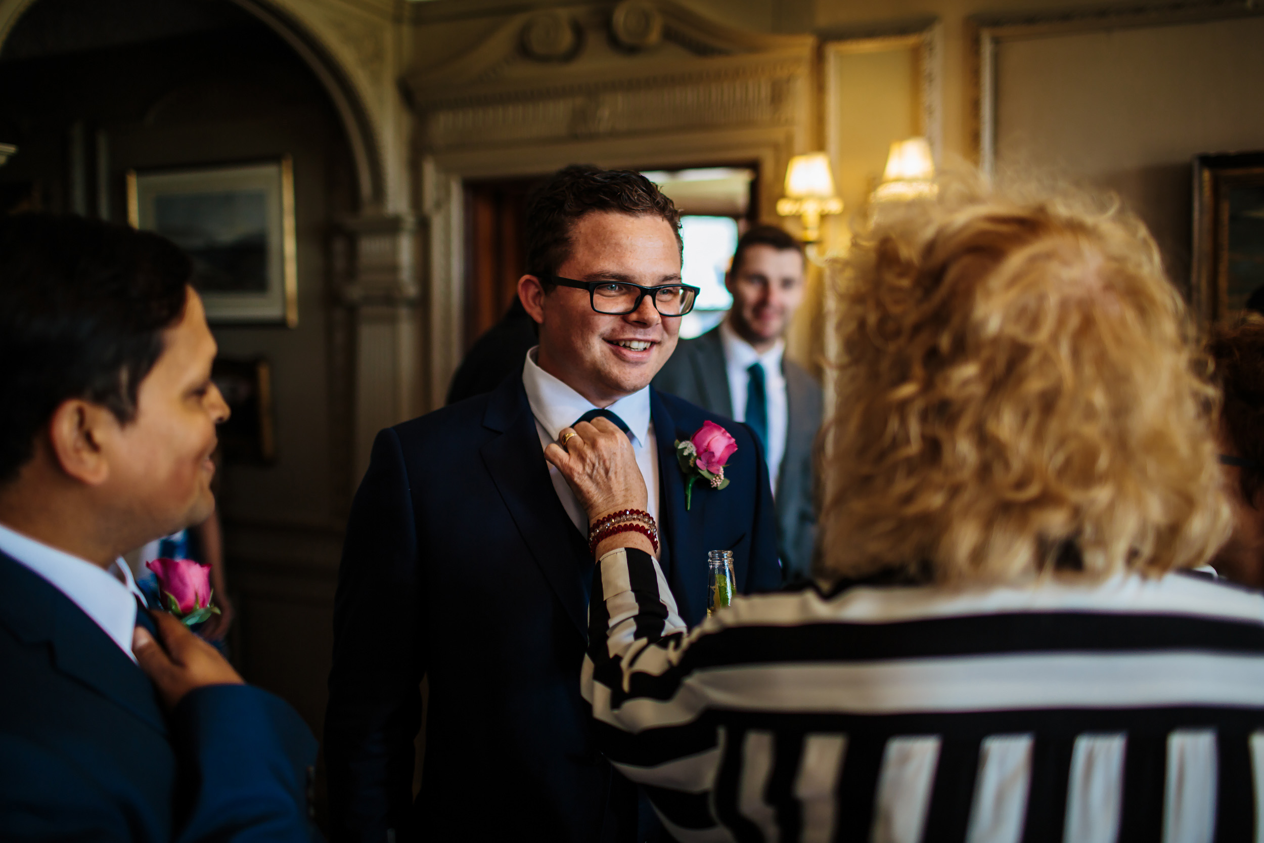 Grooms mother adjusts his tie at a wedding in Cheshire