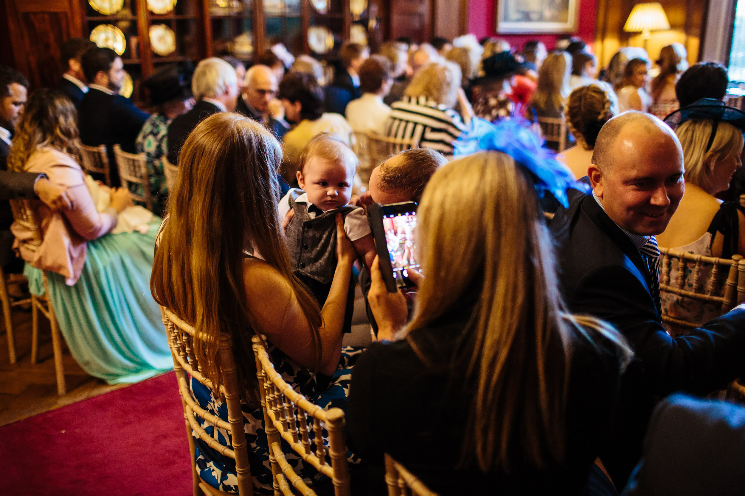 Wedding guests take photo of a baby at Thornton Manor Cheshire