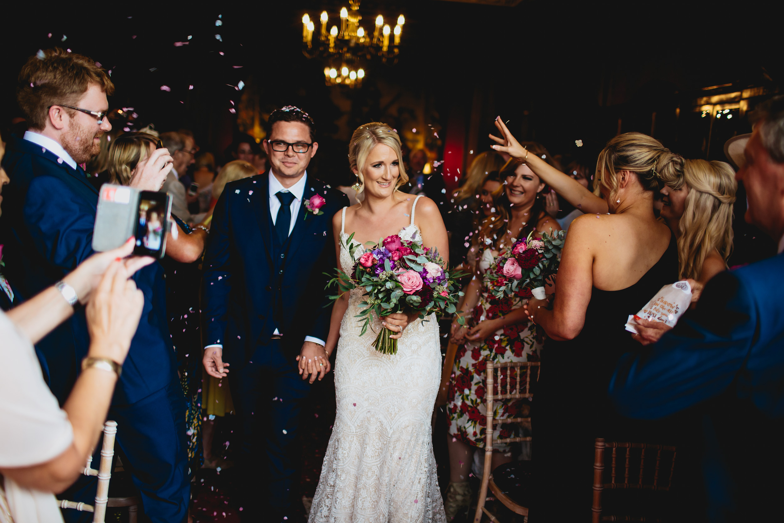 Guests throw confetti over the bride and groom at a wedding
