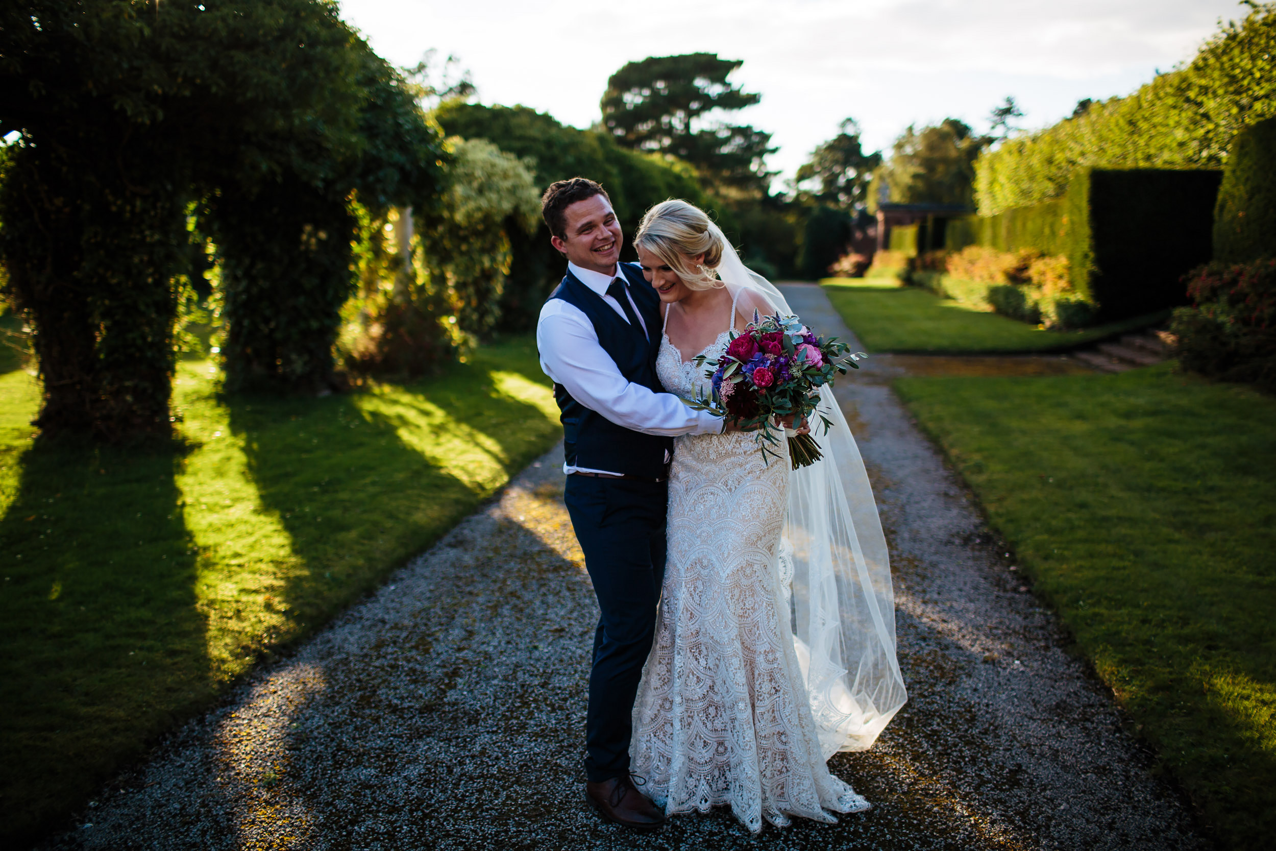 Bride and groom laughing in the gardens at Thornton Manor Cheshire