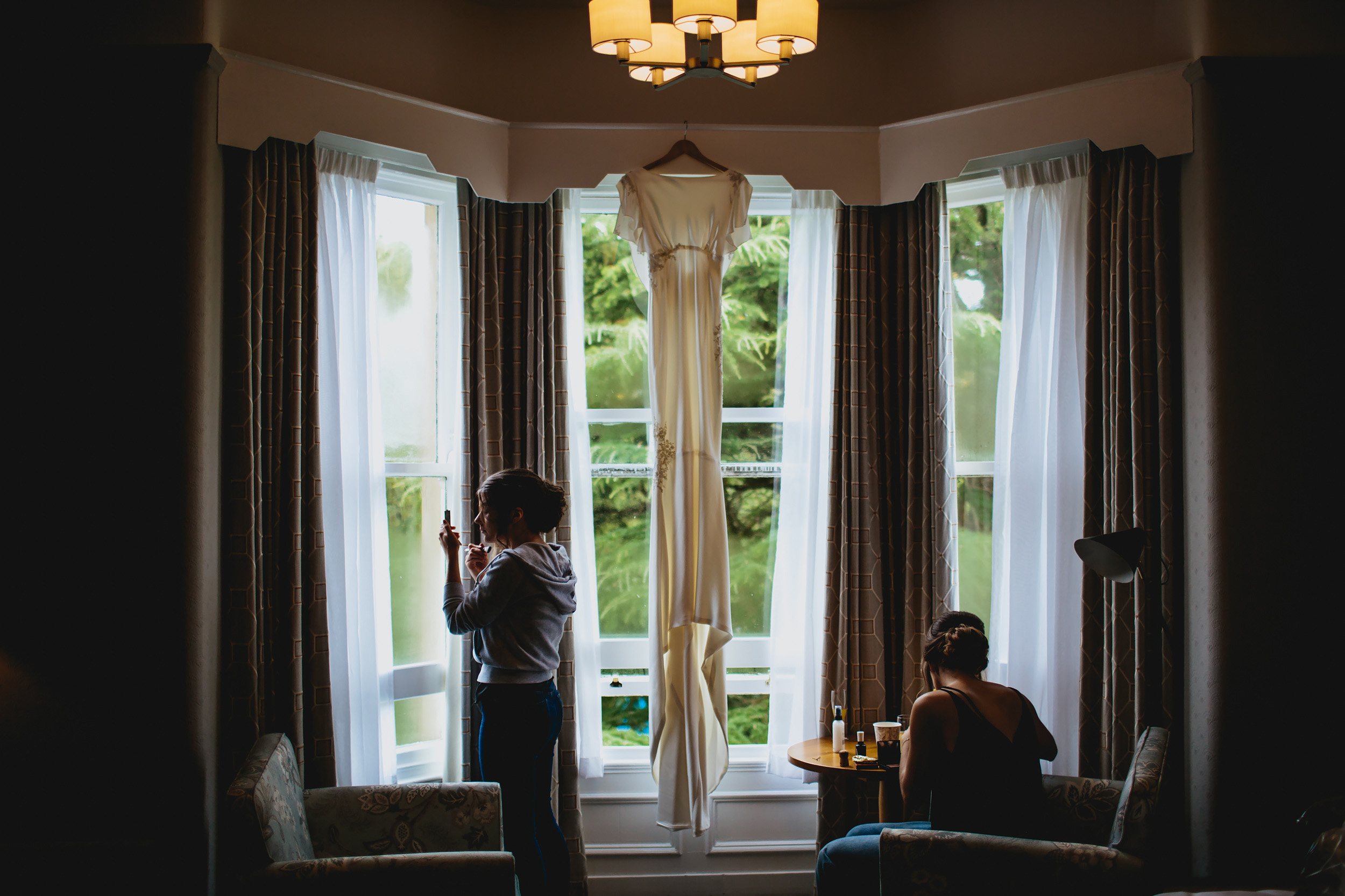 Wedding dress hanging in the window while bridesmaids apply make up