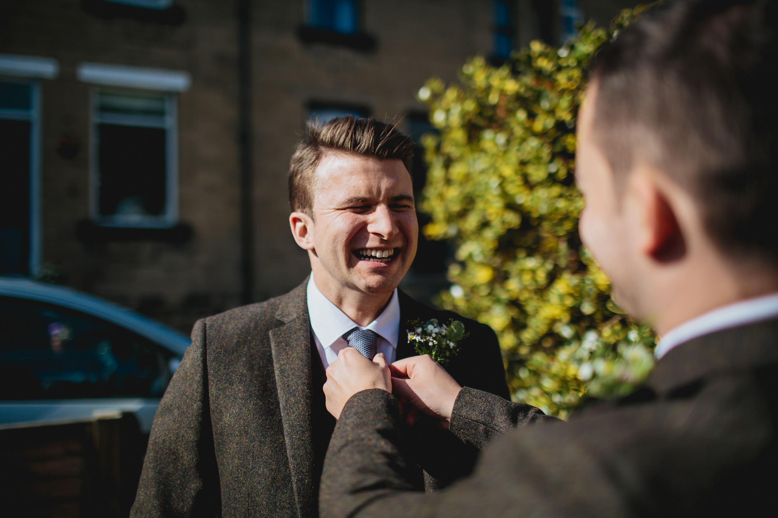 Best man helps the groom with his tie at his wedding in Yorkshire